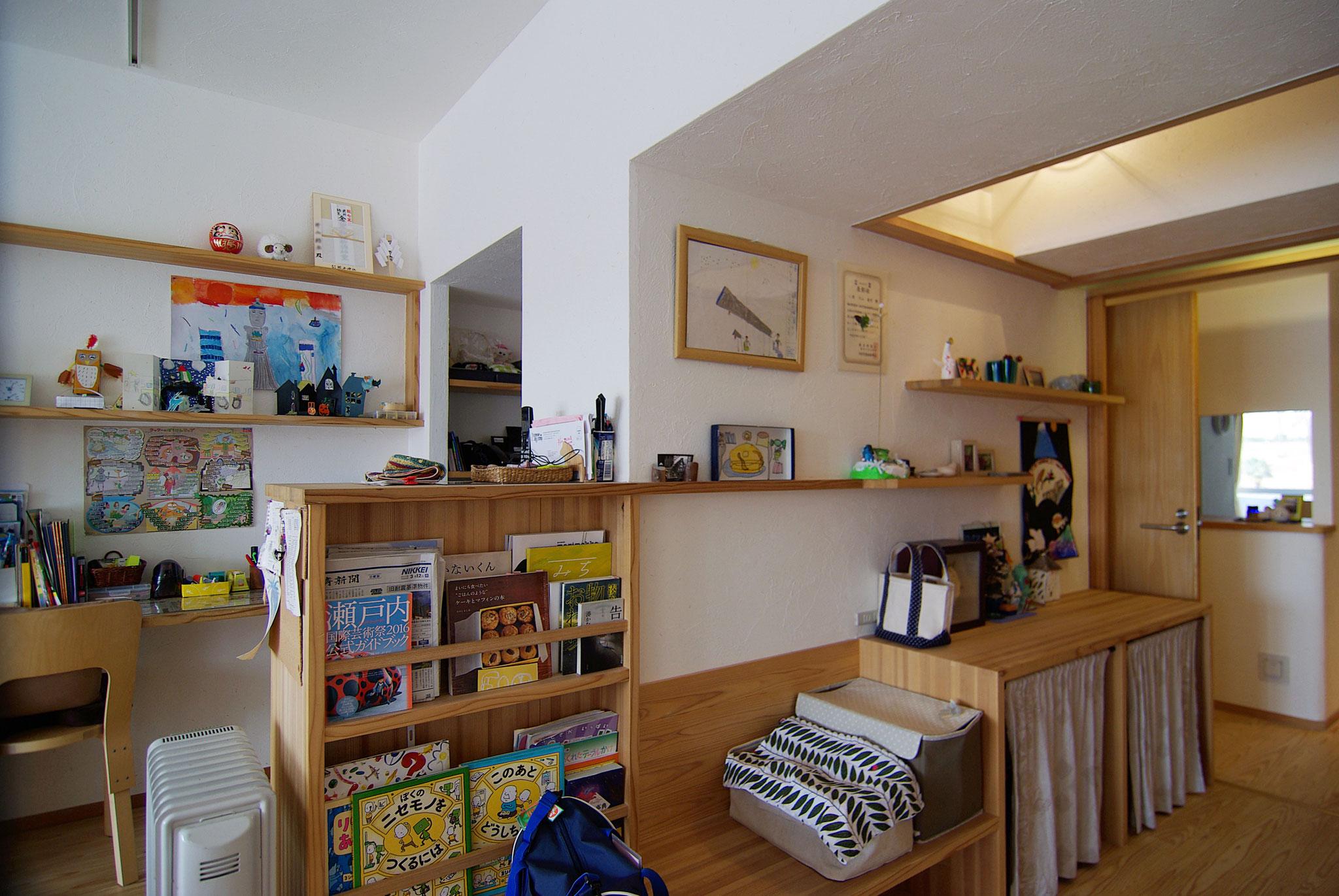 南北をつなぐ広い廊下は、風通しのよい読書スペースや住人それぞれの趣味のものなどを展示するギャラリースペースに。廊下上部には天袋を設置。