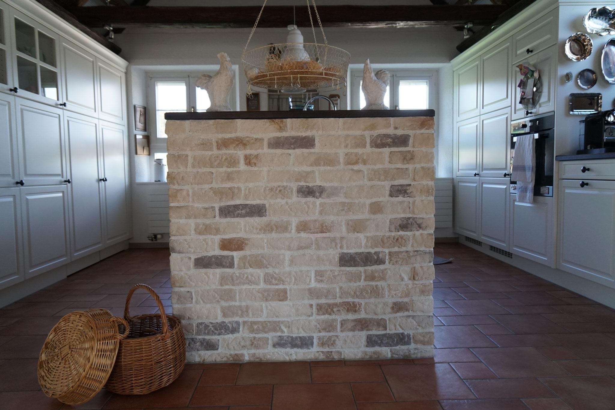 Eine Steinmauer vollendet die Landhausküche.