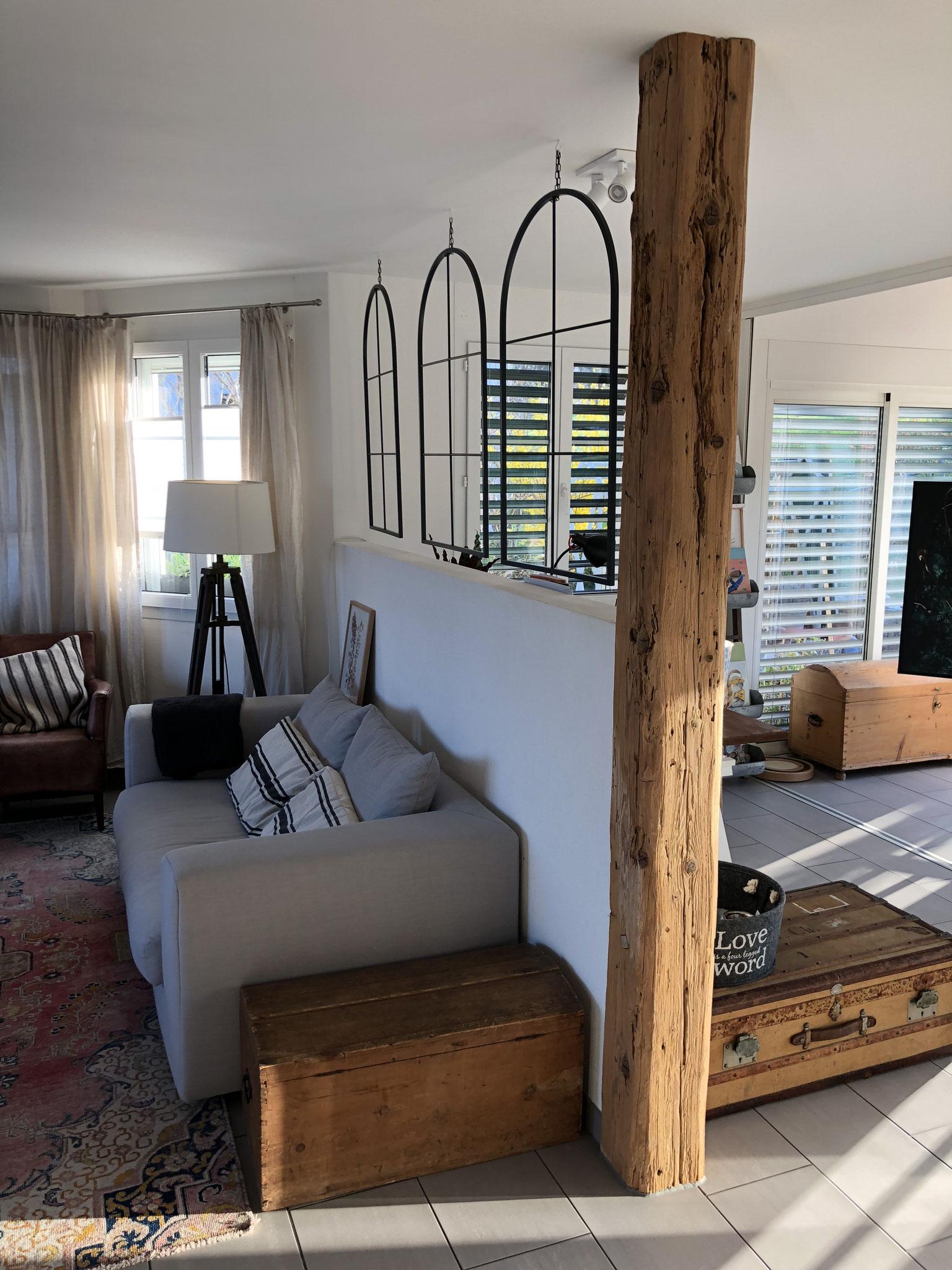 Ein bearbeiteter Holzbalken verschönert das Wohnzimmer.