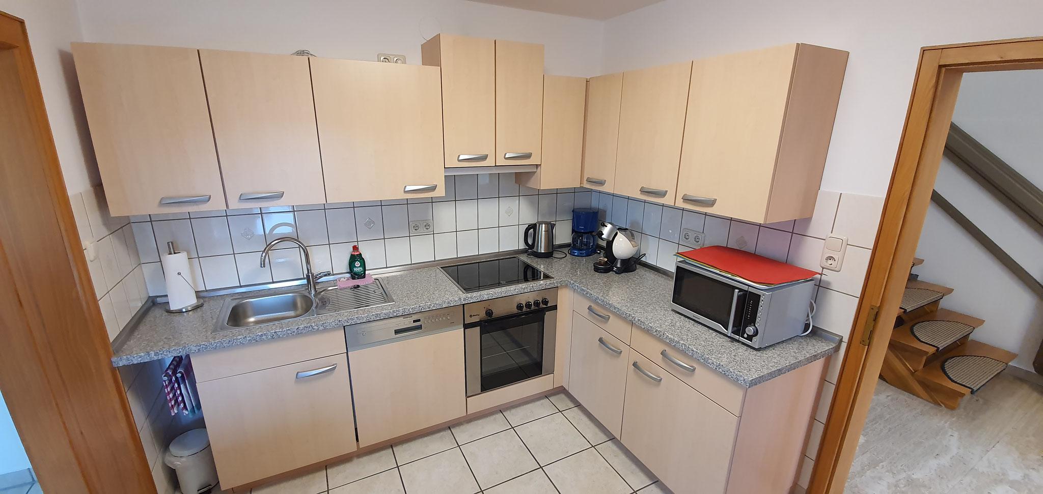 moderne Küche mit Geschirrspüler, Backofen, Kühlschrank, etc.