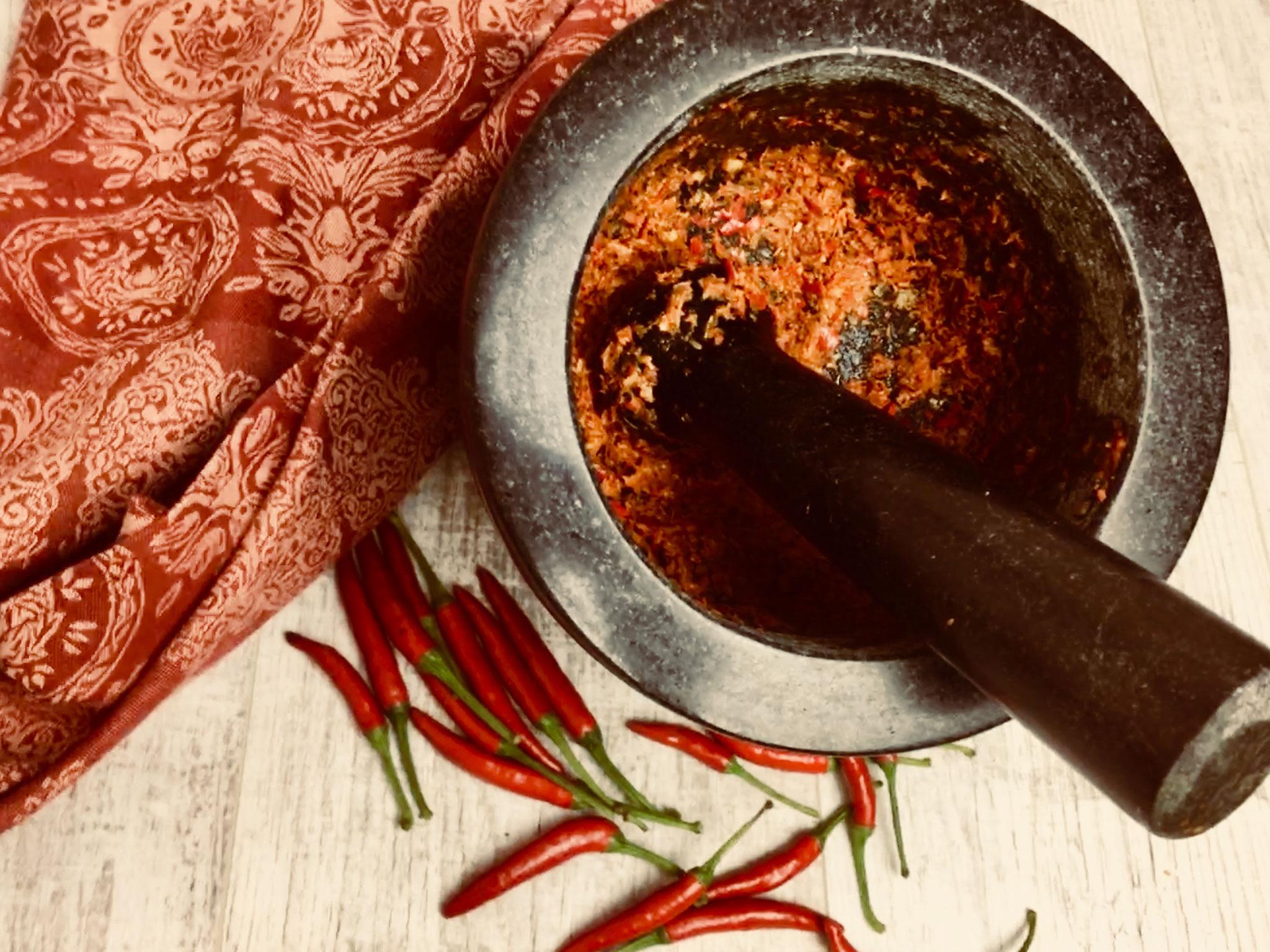 Mörser mit Chilis hier entsteht ein tolles Curry
