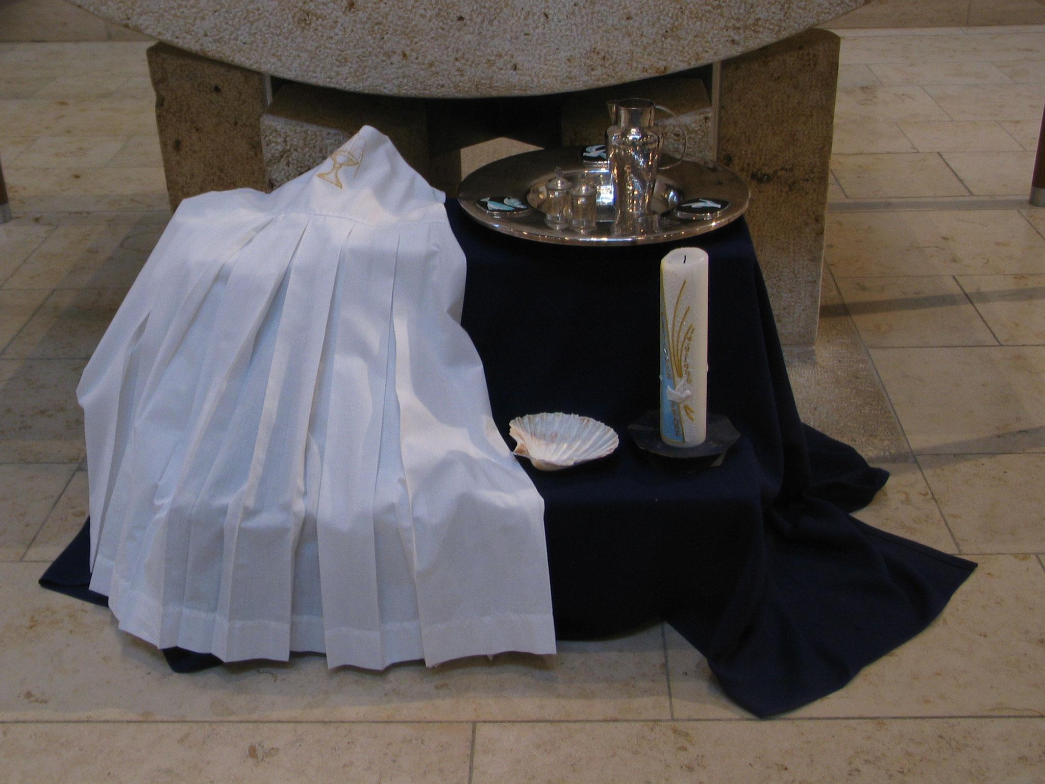 Vor dem Altar in der Ellgauer St. Ulrichskirche waren alle Gegenstände, die zu einer Taufe gehören, hergerichtet: Taufkleid, Taufkerze, Jakobsmuschel, Weihwasser und Chrisam