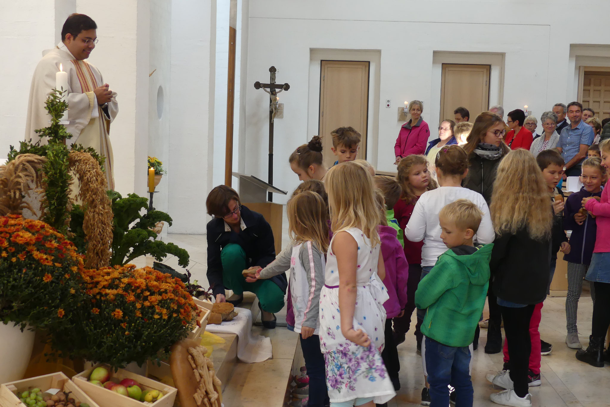 Ombeline Monfroy vom Vorbereitungsteam teilt am Ende der feierlichen Eucharistie das Brot mit den zahlreichen Kindern