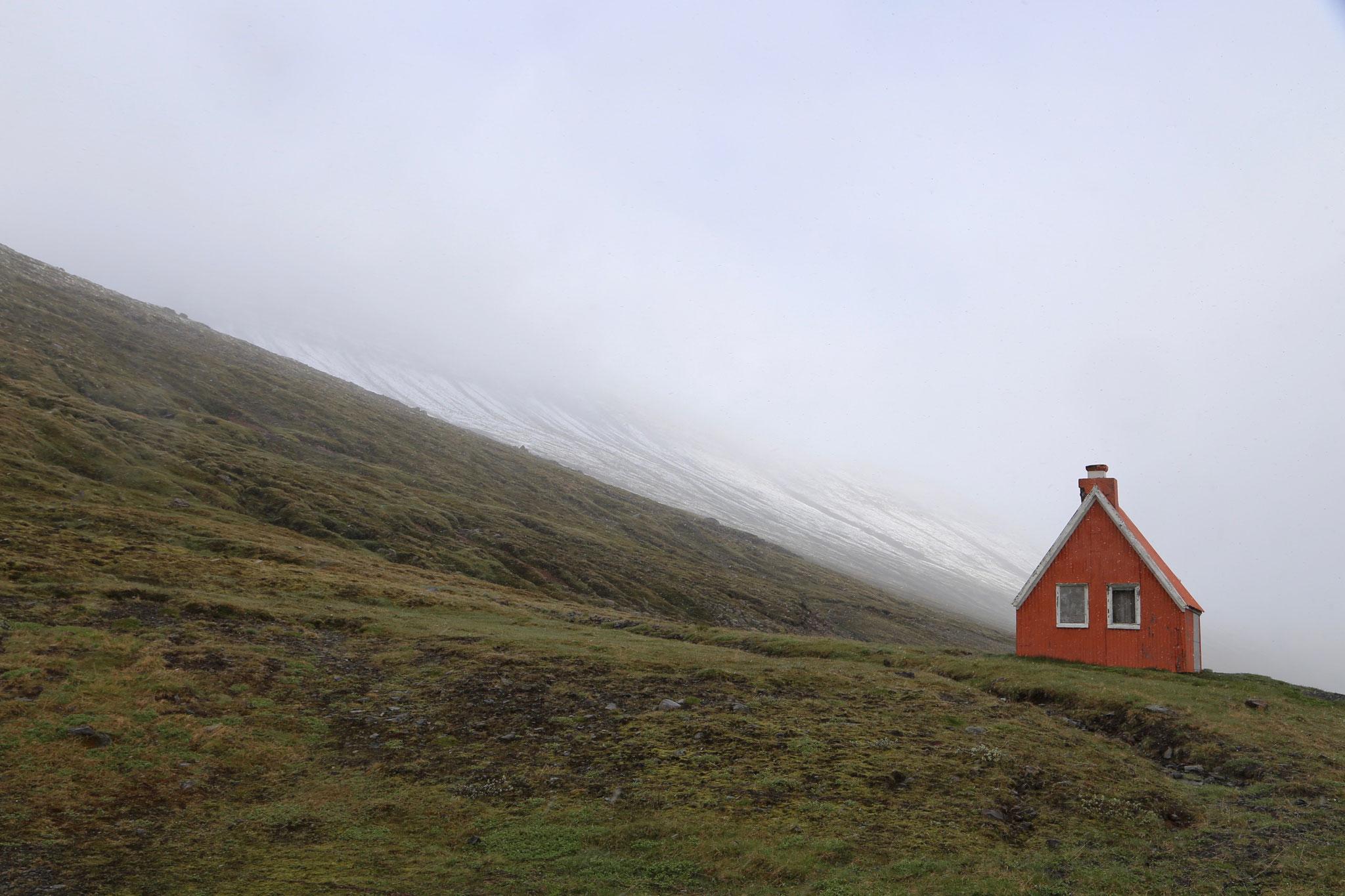 Ein rotes Häuschen im Schneetreiben im Osten Islands