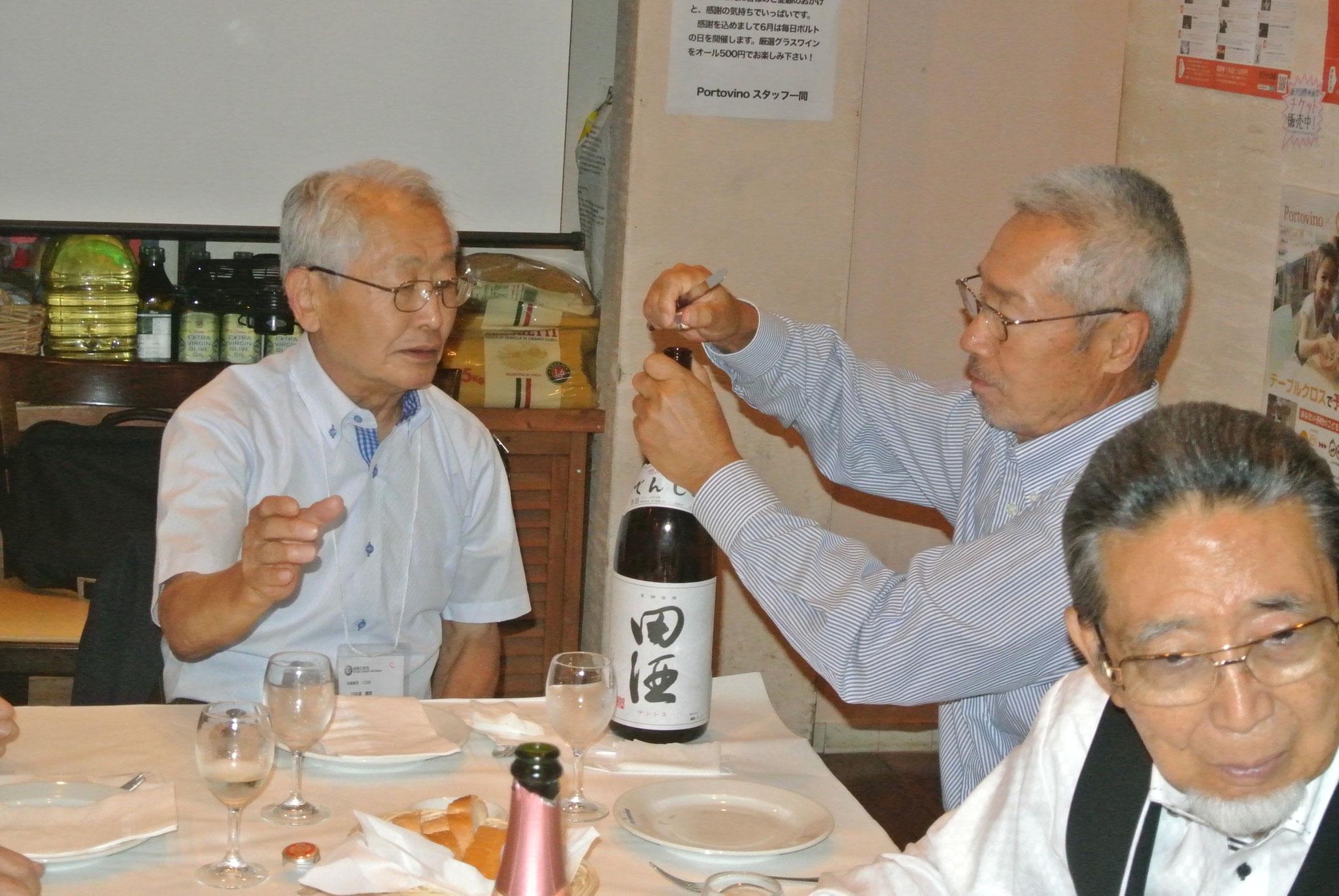和田名誉利き酒師の前で小林副会長名酒田酒を開ける右岸野講師