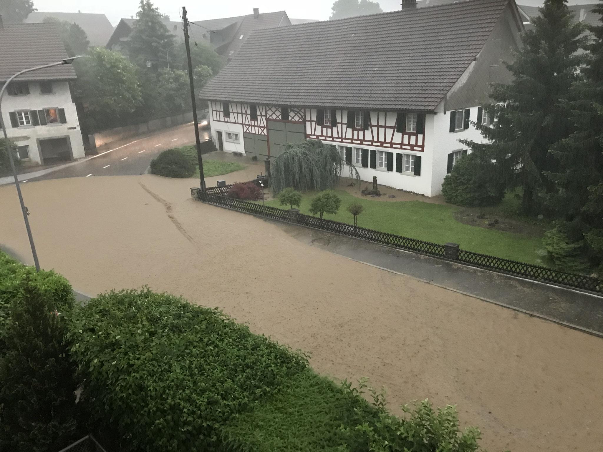 Über die Strasse abfliessendes Hochwasser (Bild: Private)