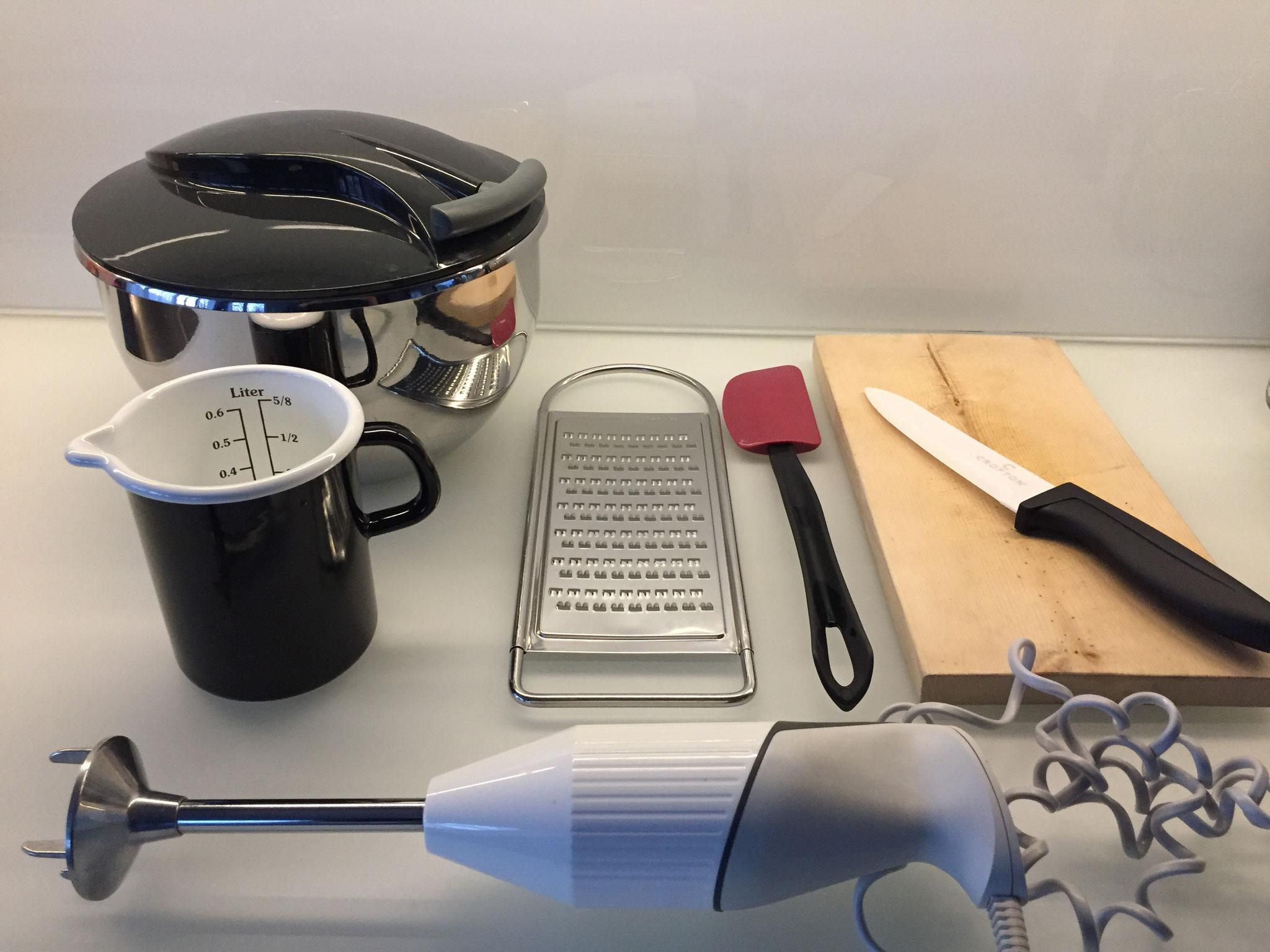 Eine Salat Schleuder, Mixer, Masskrug, Brett, Messer, Raffel, Mörser und einen Nuss Knacker.