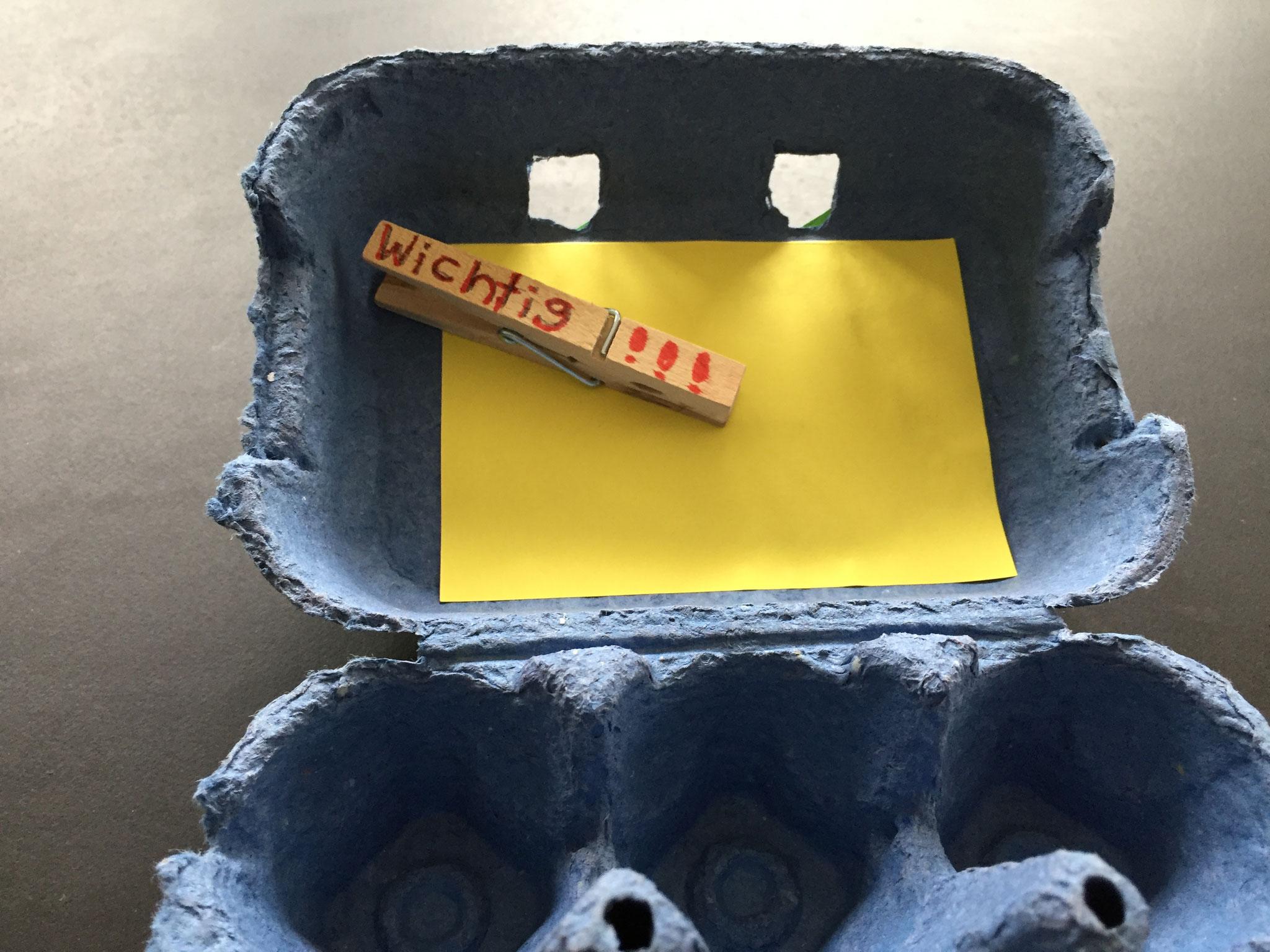Du klebst die Klammer in den Deckel. Pass auf, dass sich die Schachtel noch gut schliessen lässt. Wenn nicht, musst du die Klammer verschieben.