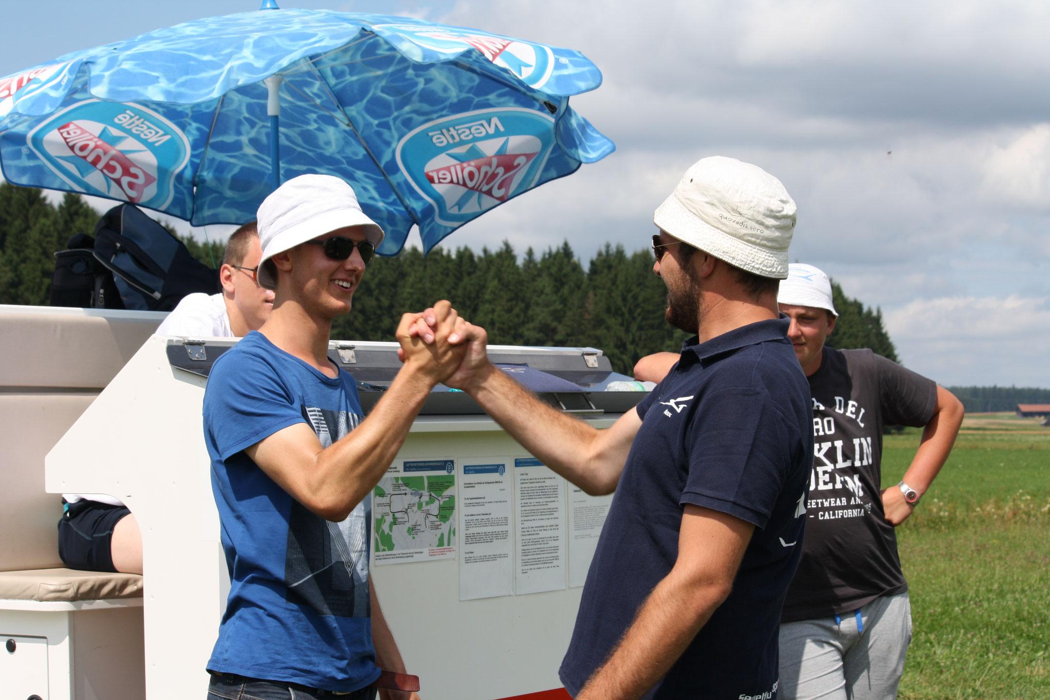 Fluglehrer Max gratuliert seinem Flugschüler Pascal zum ersten Alleinflug
