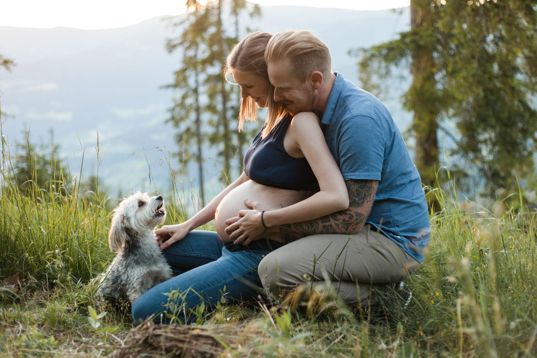 Babybauchfoto mit Hund im Wald