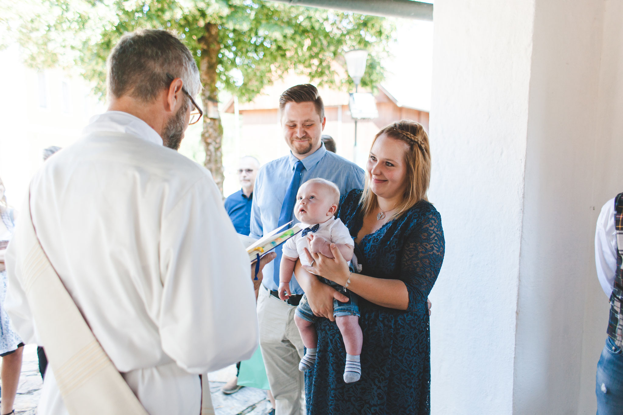Taufe vor der Kirche mit dem Taufkind