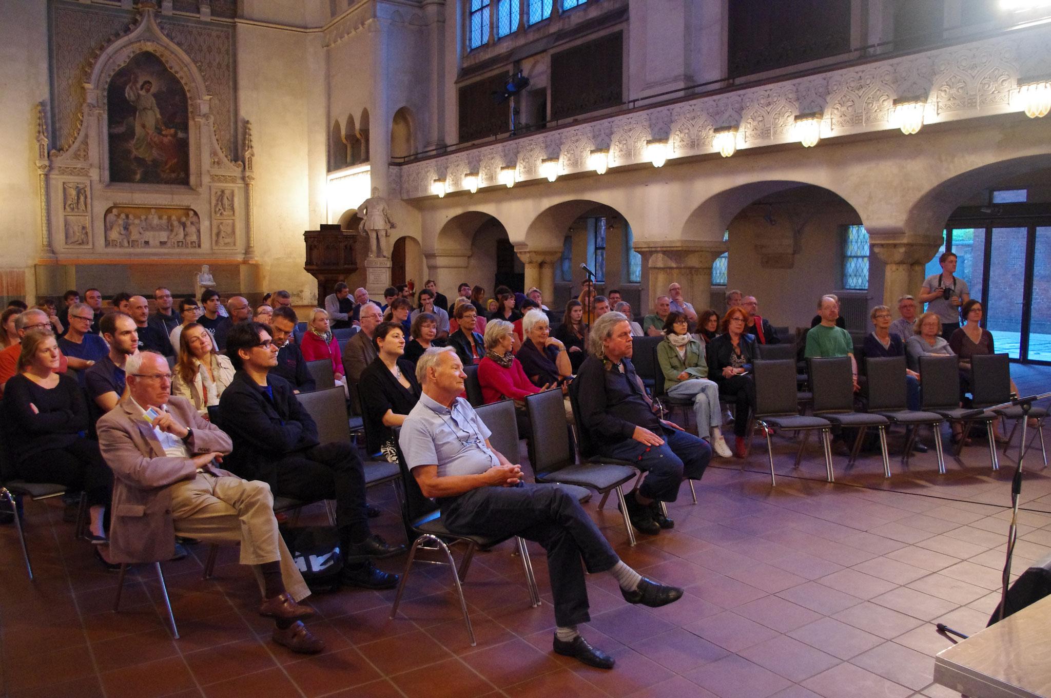 Zuhörer verfolgen aufmerksam die Ausführungen der Kandidaten