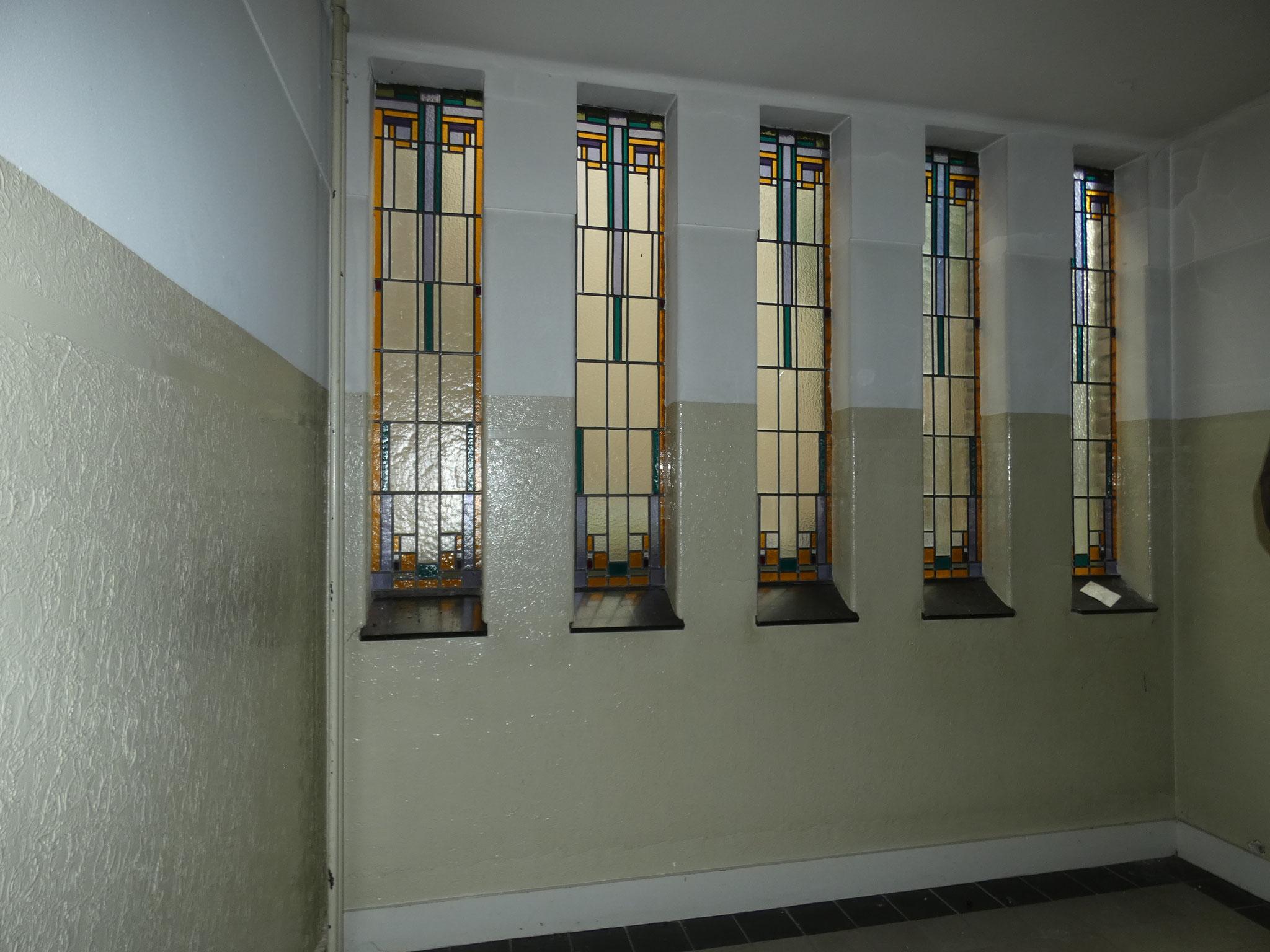 glas-in-lood in een van de trappenhuizen van het hoofdvolume.