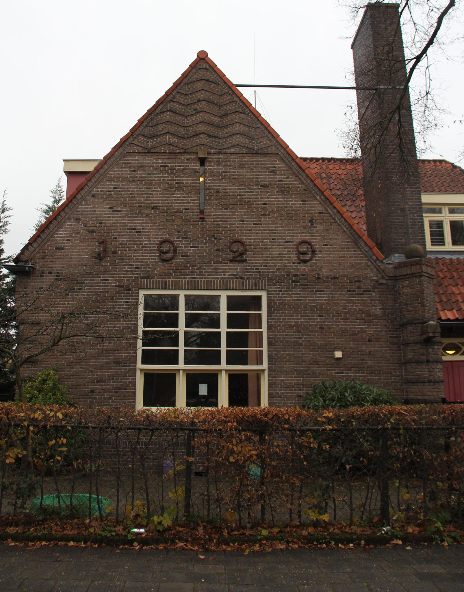 Noordoostgevel met opvallend hoge schoorsteen en plantenbak en fraaie detaillering in de geveltop.