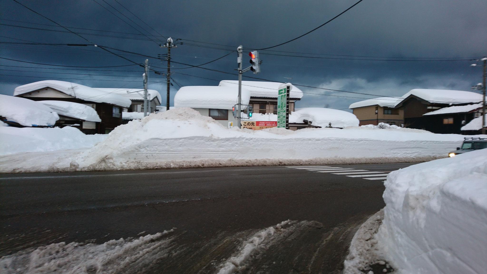 踏切のそばにある国道8号線の交差点。歩道の除雪はなく、国道を歩く必要があります。