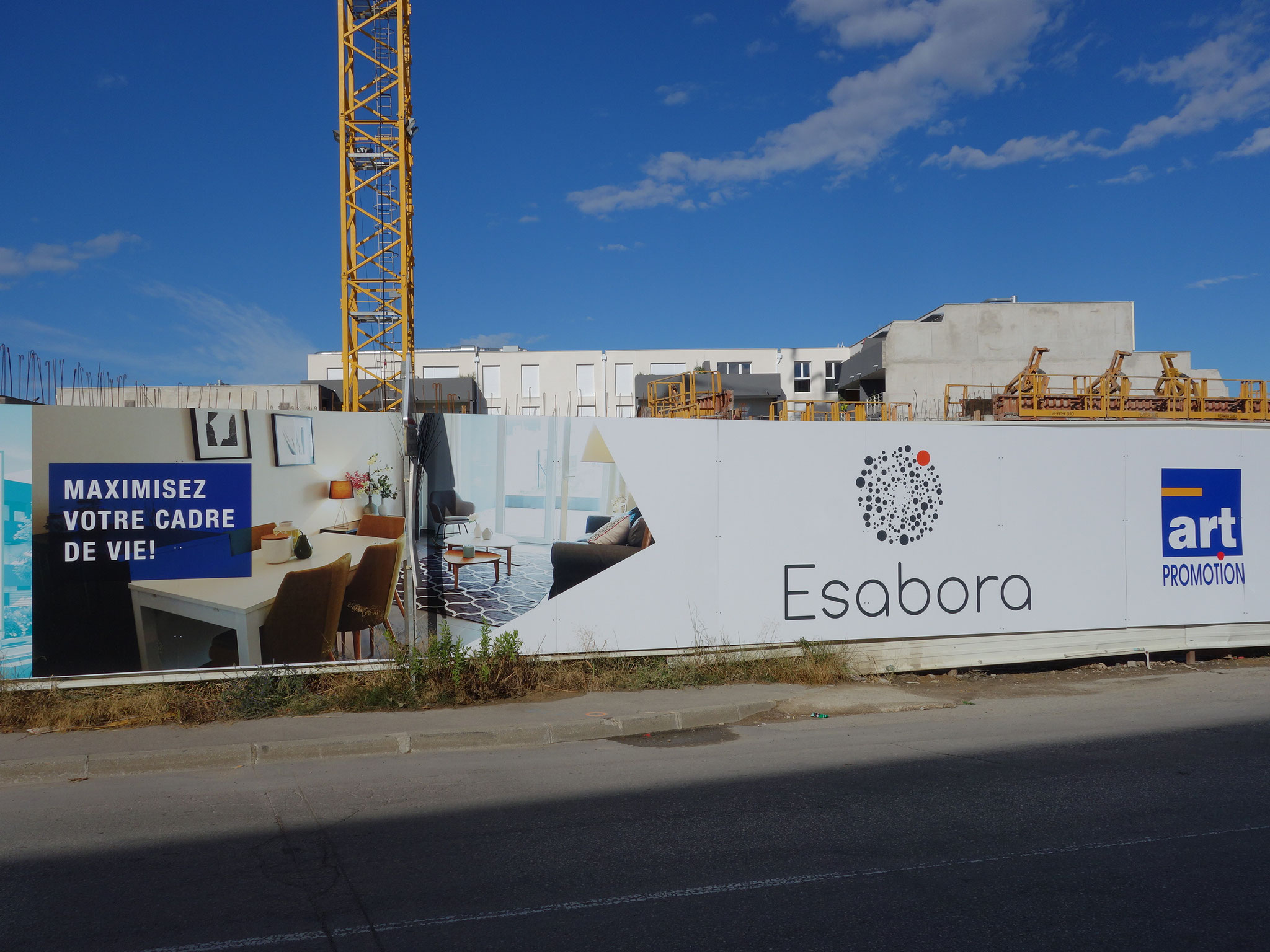 Panneaux de chantier avec la photo de l'appartement témoin