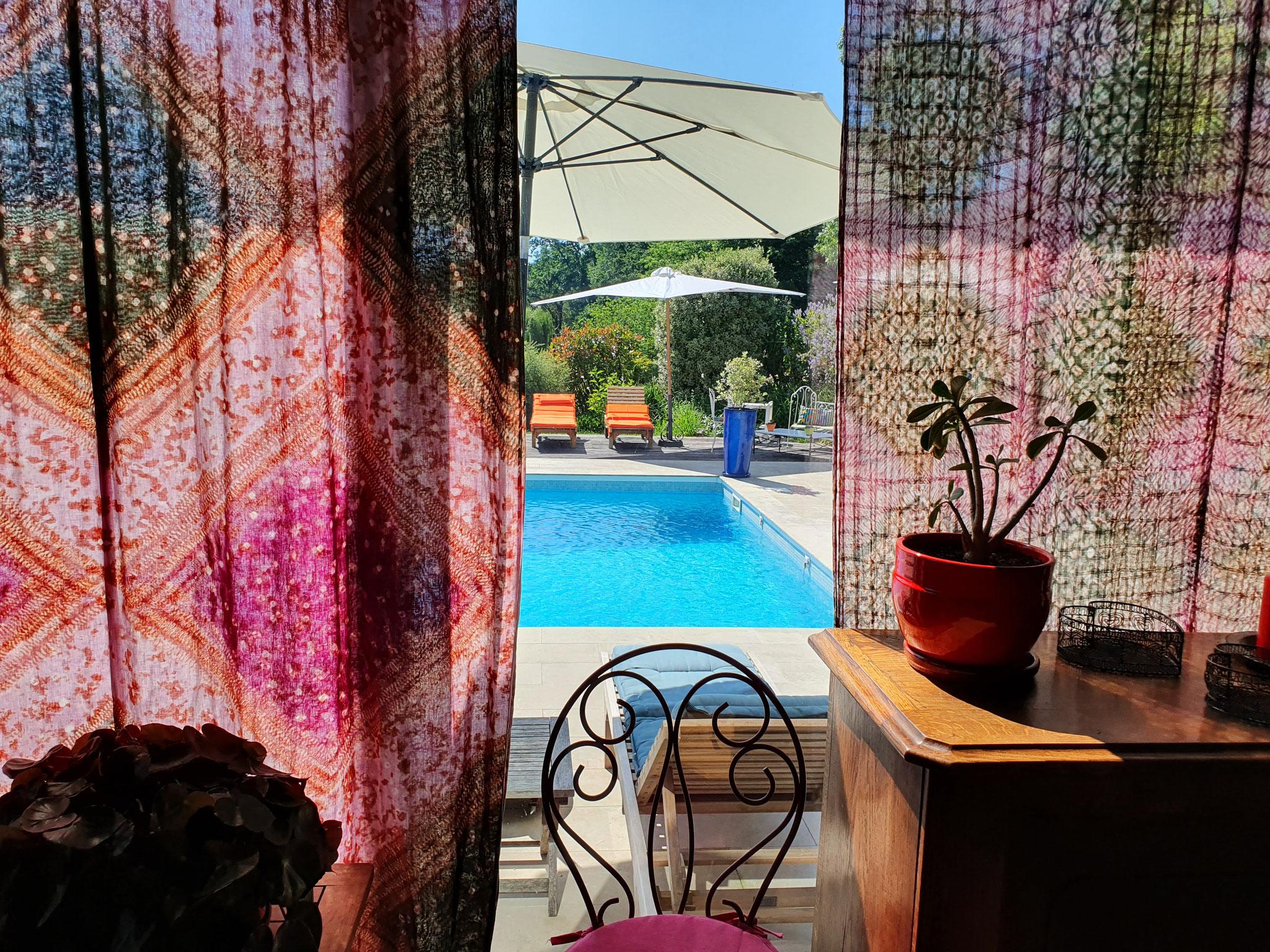 domaine de Millox aperçu de la piscine à travers les rideaux de la véranda