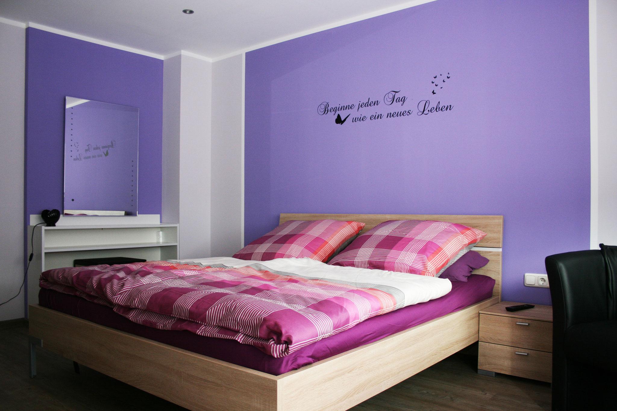 Modernes Schlafzimmer mit einem Schminktisch, Schrank und Flachbildfernseher