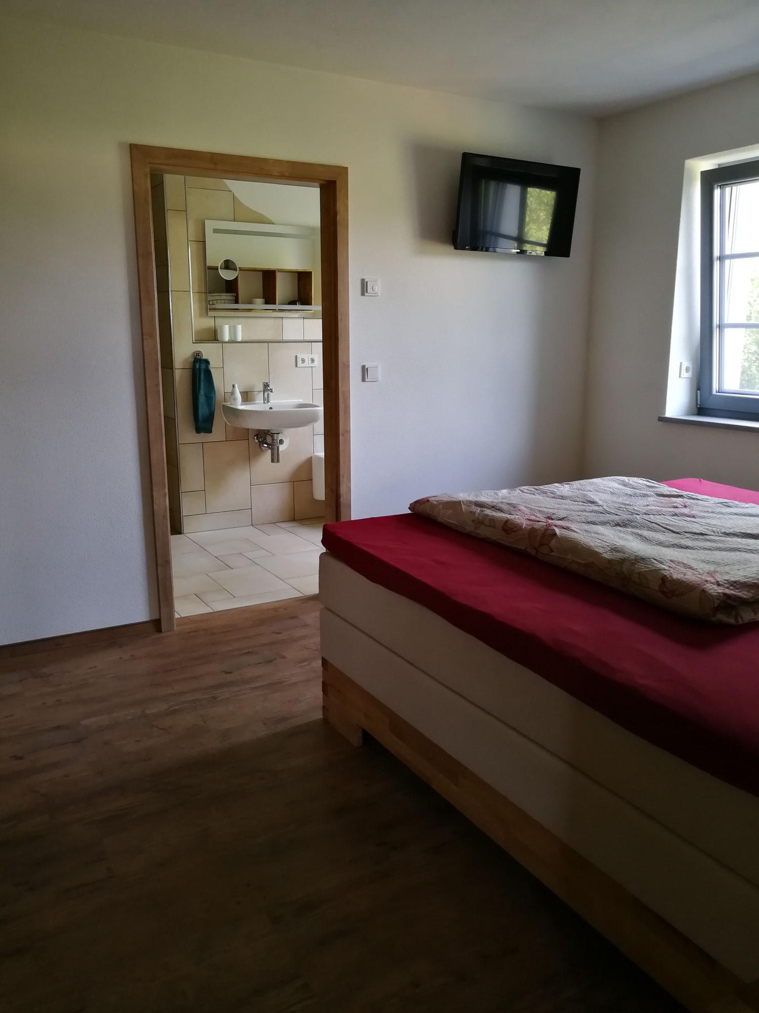 Schlafzimmer 1 mit Blick ins Bad