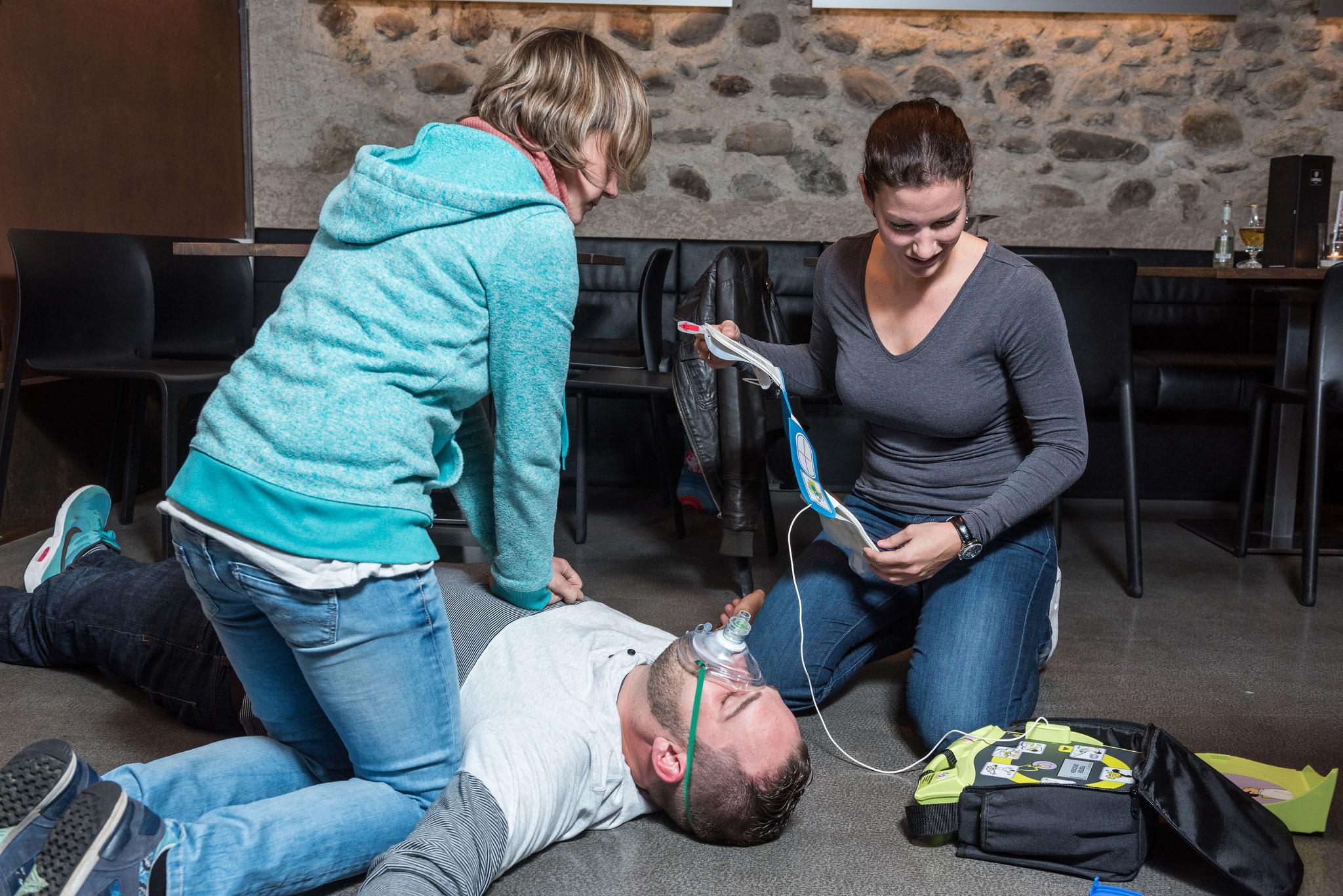 Sobald ein Defibrillator vor Ort ist den Anweisungen folgen