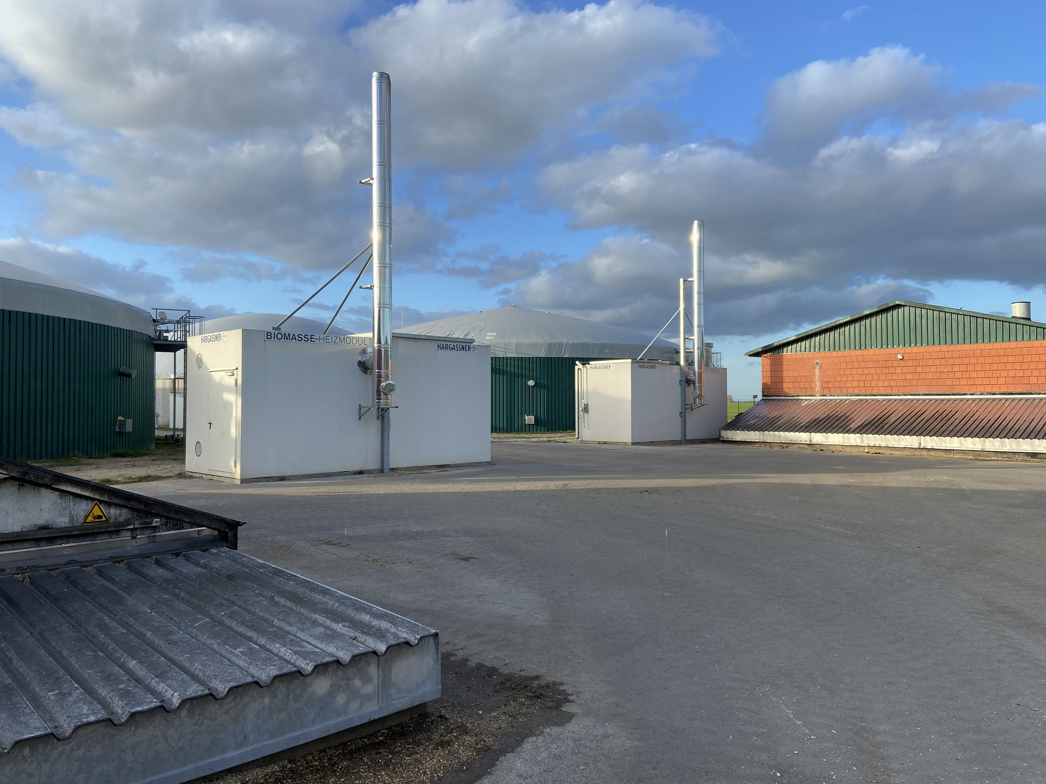 Ansicht auf die beiden Biogasanlagen und die Hackschnitzelcontainer