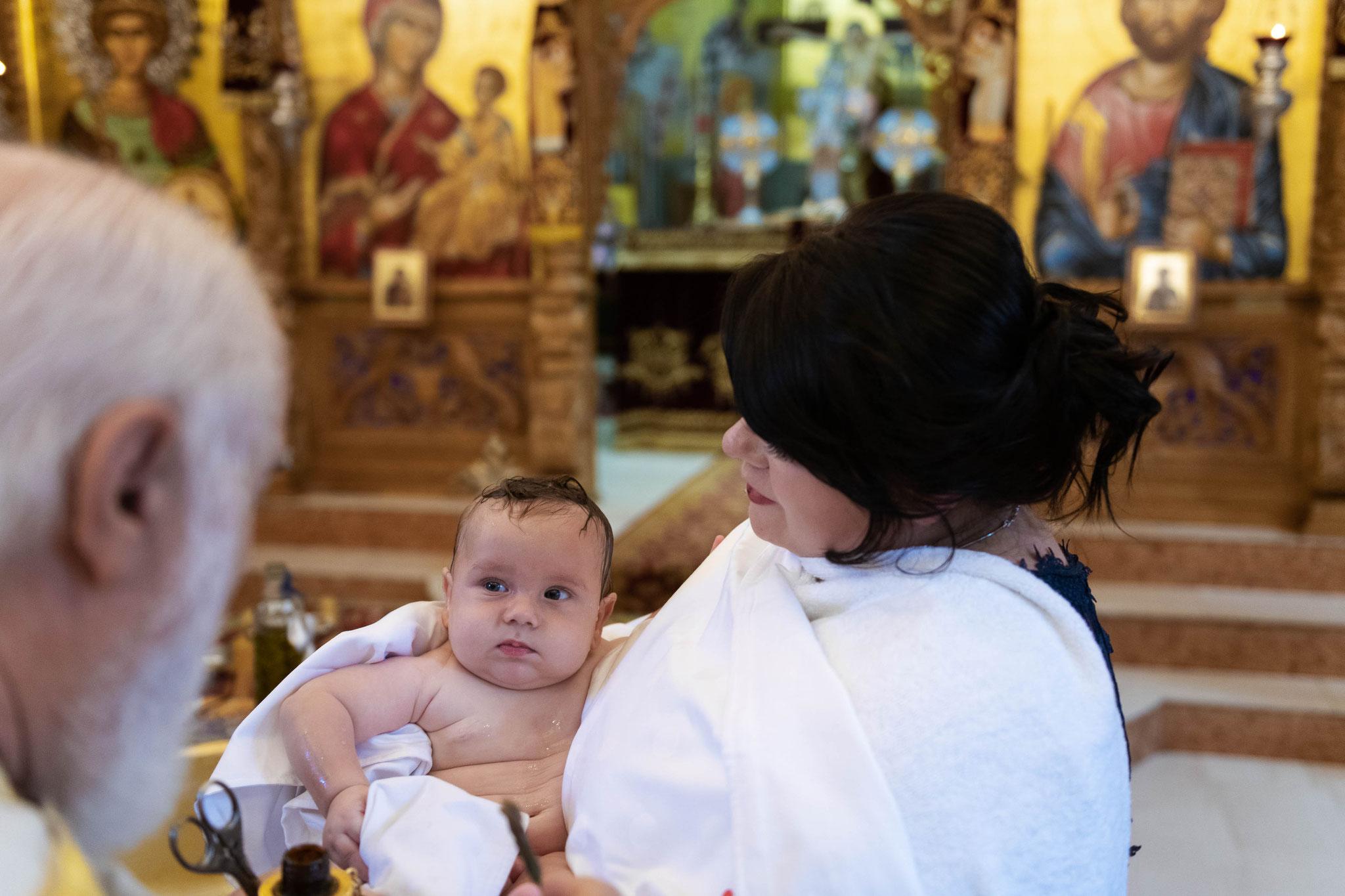 Der überraschende Blick des getauften Kindes