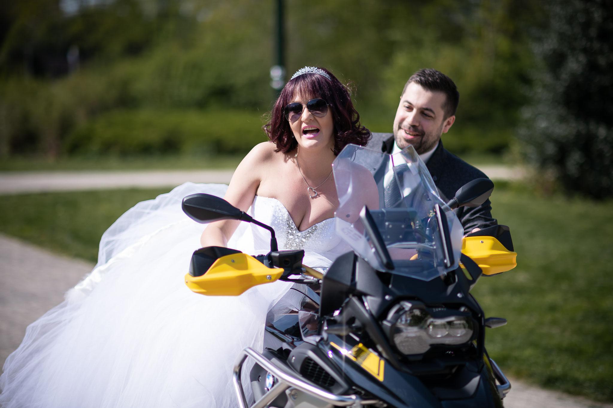 Braut und Bräutigam haben voll Spß bei dem Fotoshooting mit dem Motorrad