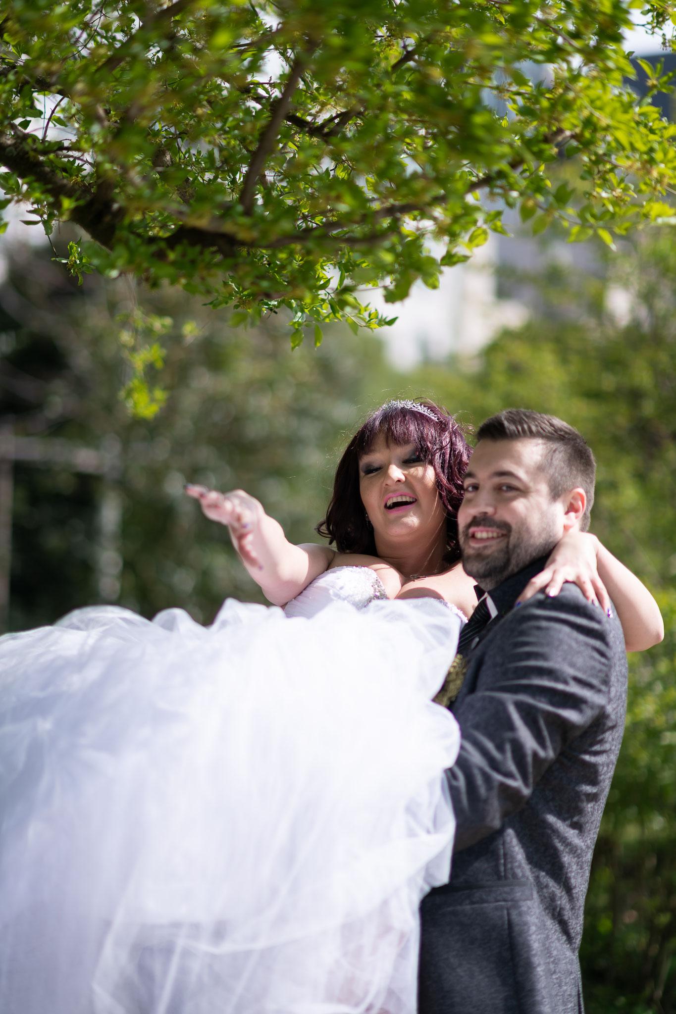 Bräutigam trägt seine Braut auf den Händen