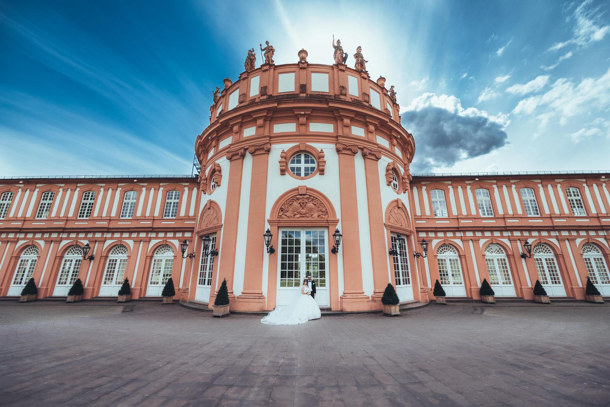 Brautpaar mit dem Schloss Biebrich im Hintergrund aus einem Weitwinkelobjektiv