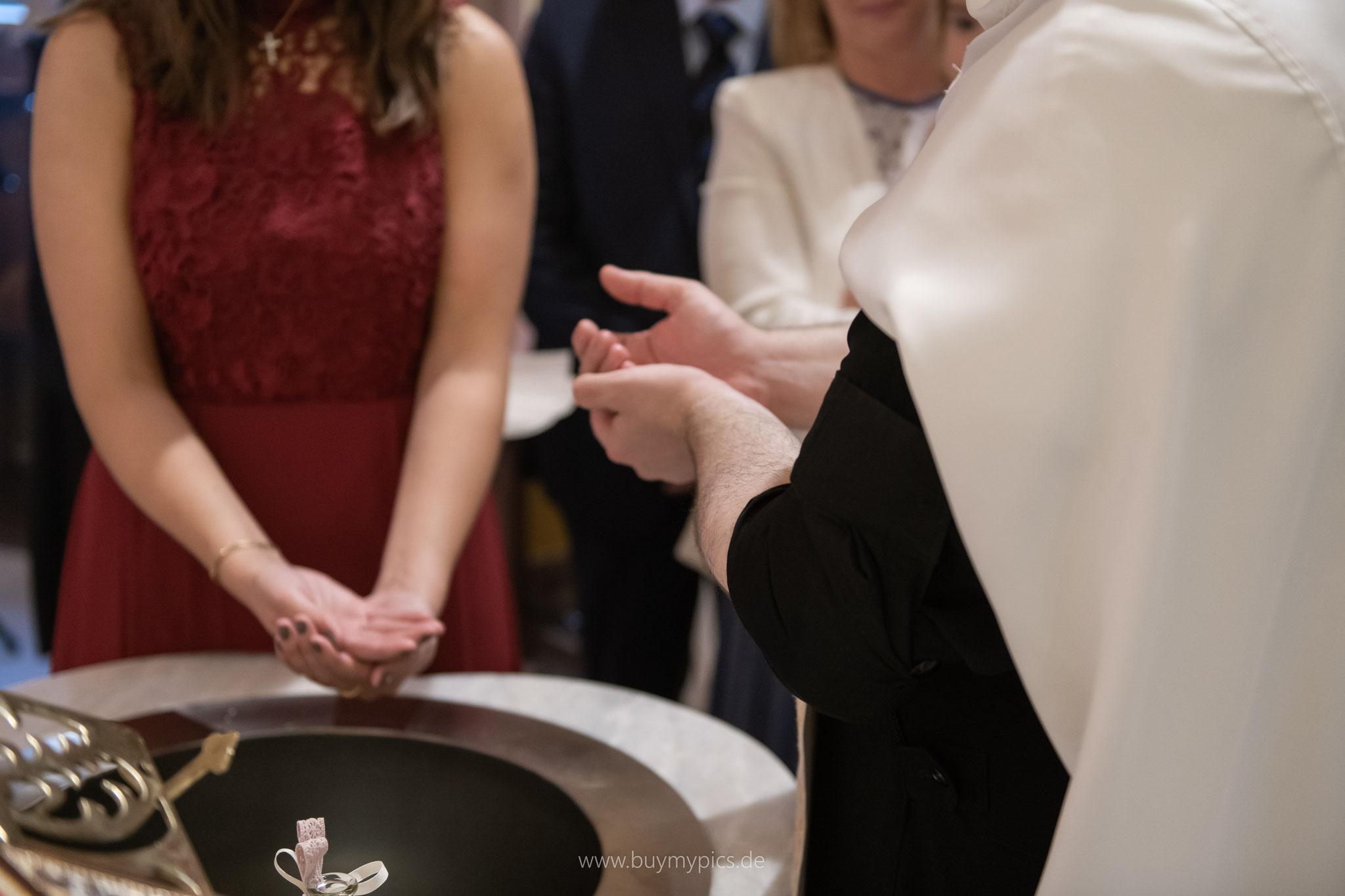 Priester erklärt den Ablauf der Taufe