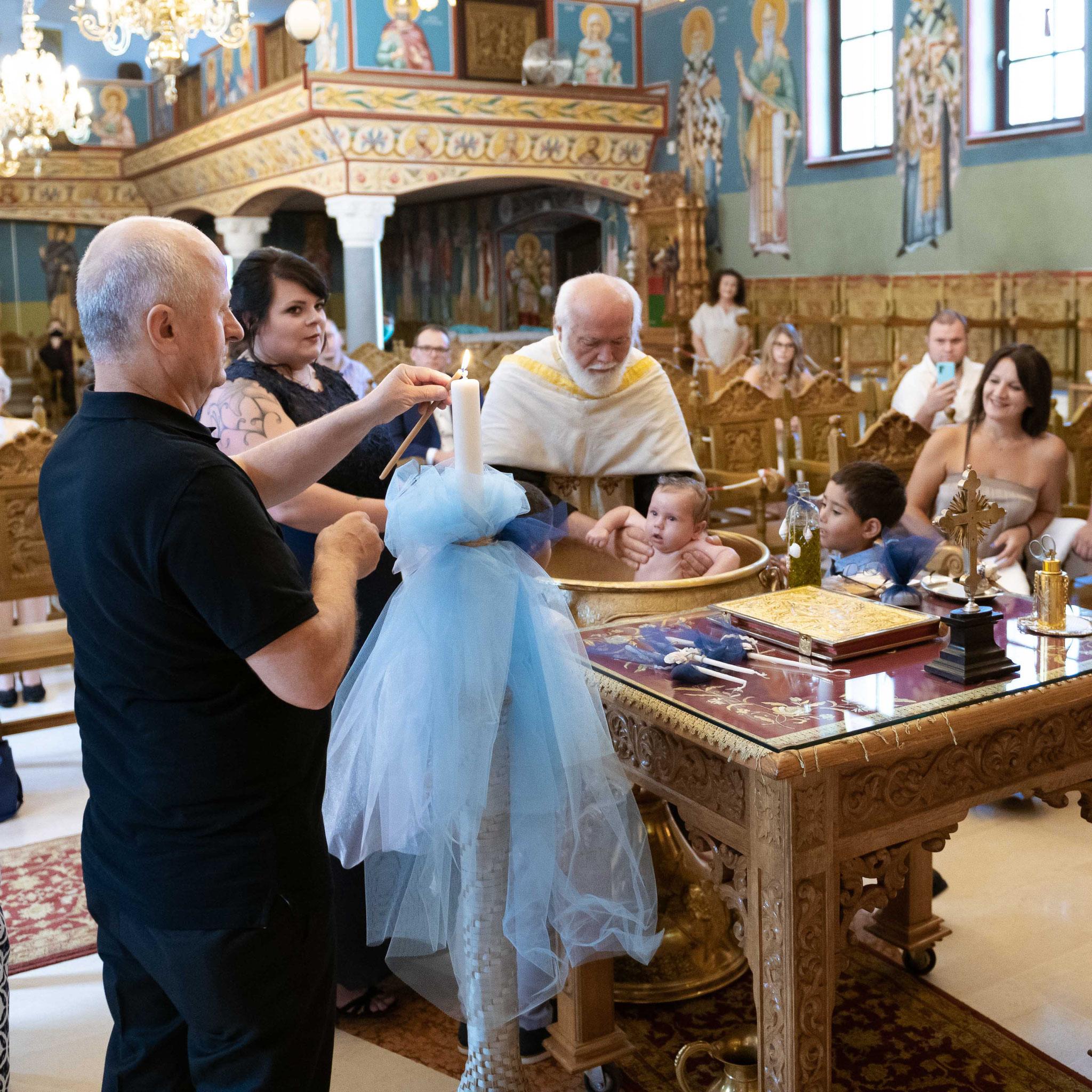 Das Kind wird vor der Taufe in den Becken gesetzt