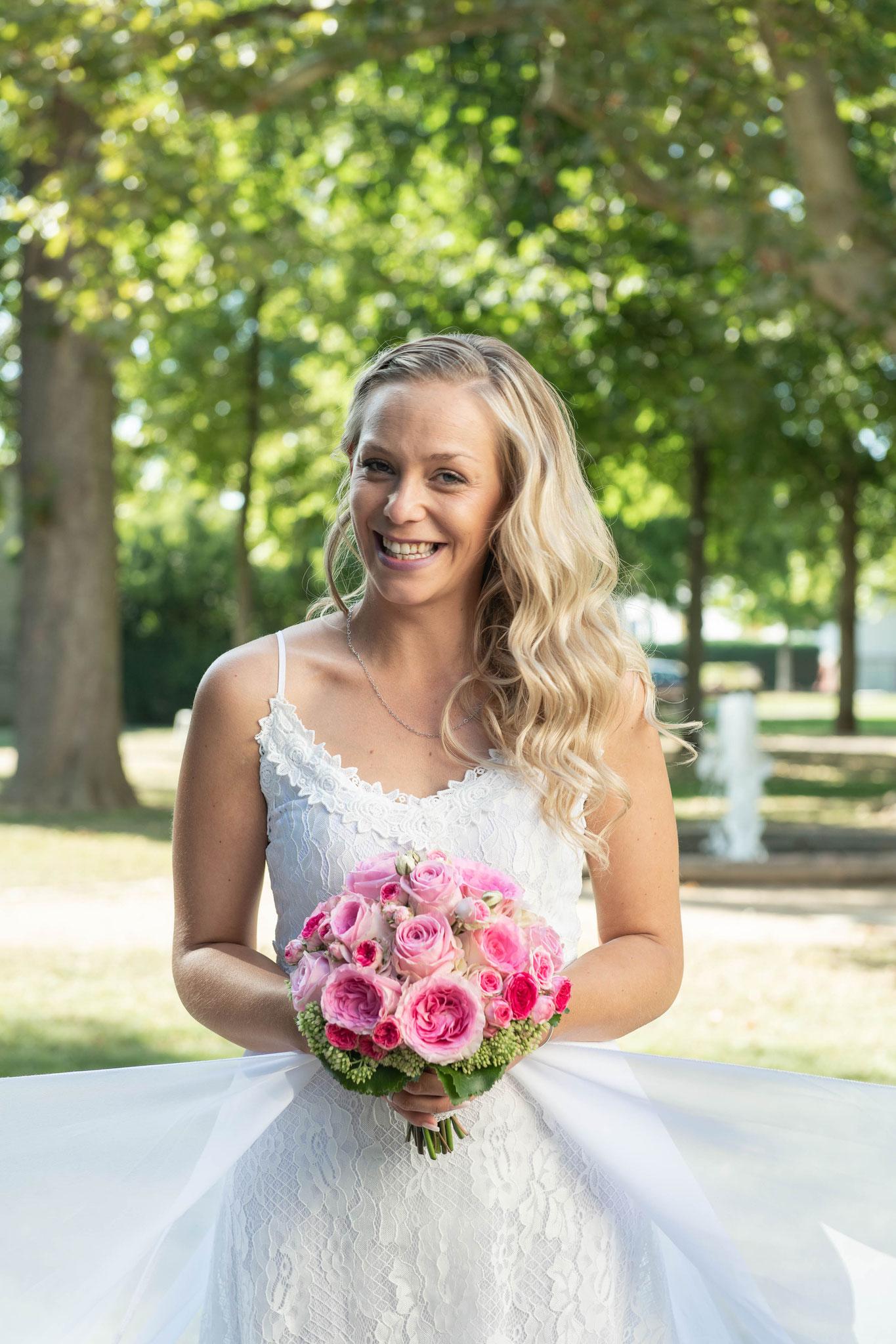Braut voller Freude mit einem Blumenstrauß