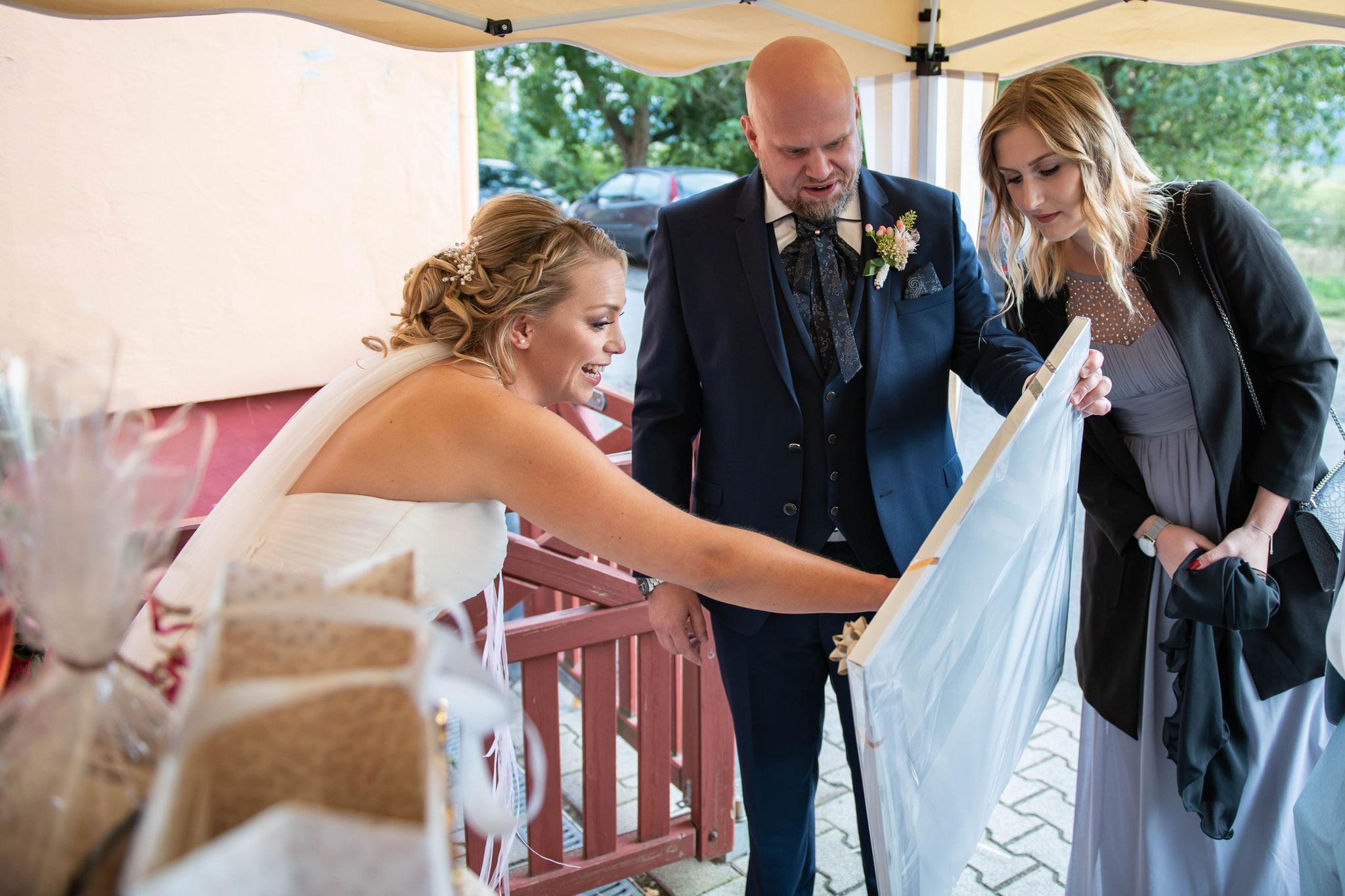 Braut betracht voller Emotionen das Geschenk der Gäste
