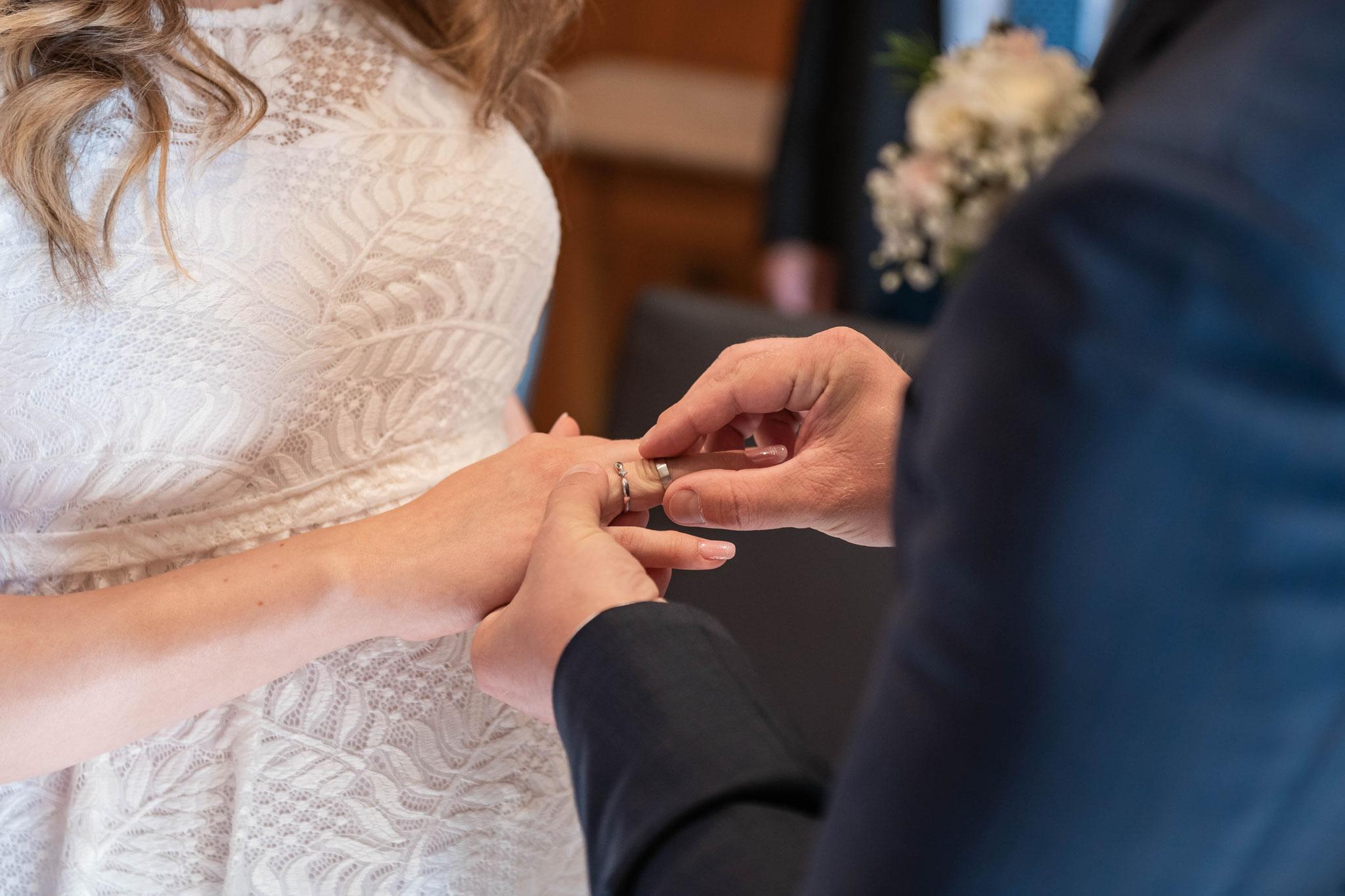 Bräutigam steckt seiner Braut den Heiratsring an den Finger