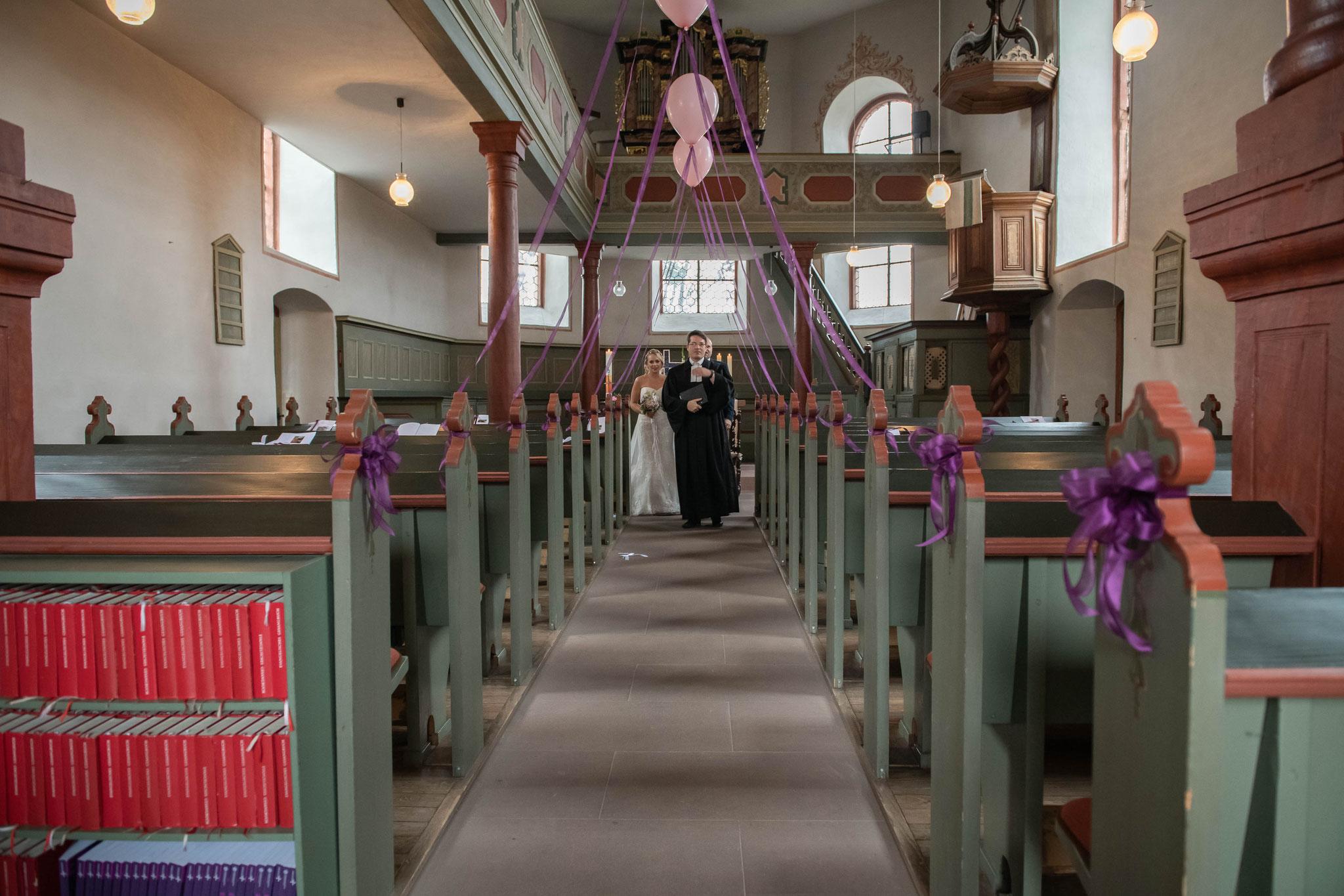 Pfarrer führt das Brautpaar aus der Kirche