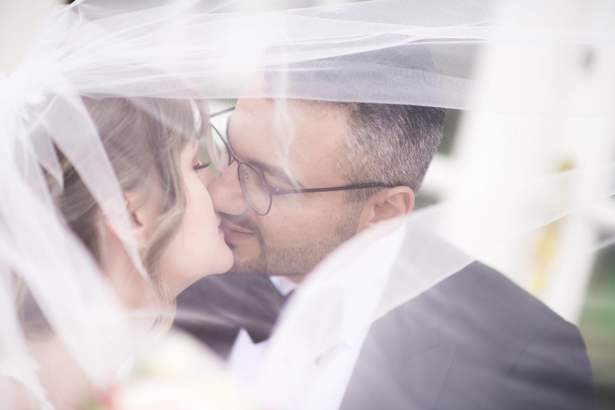 Das Brautpaar beim Küssen durch den Schleier fotografieren