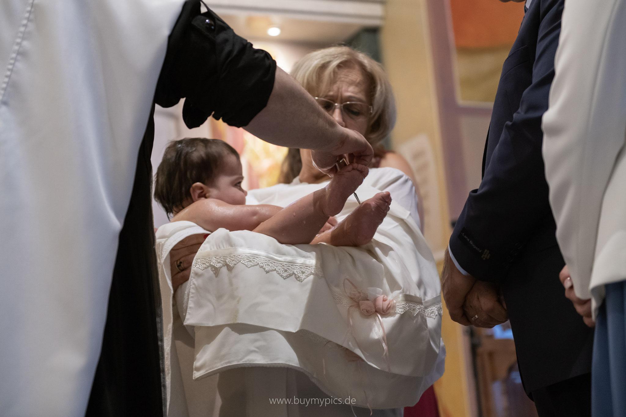 Die Füße des Kindes werden mit Olivenöl bepinselt