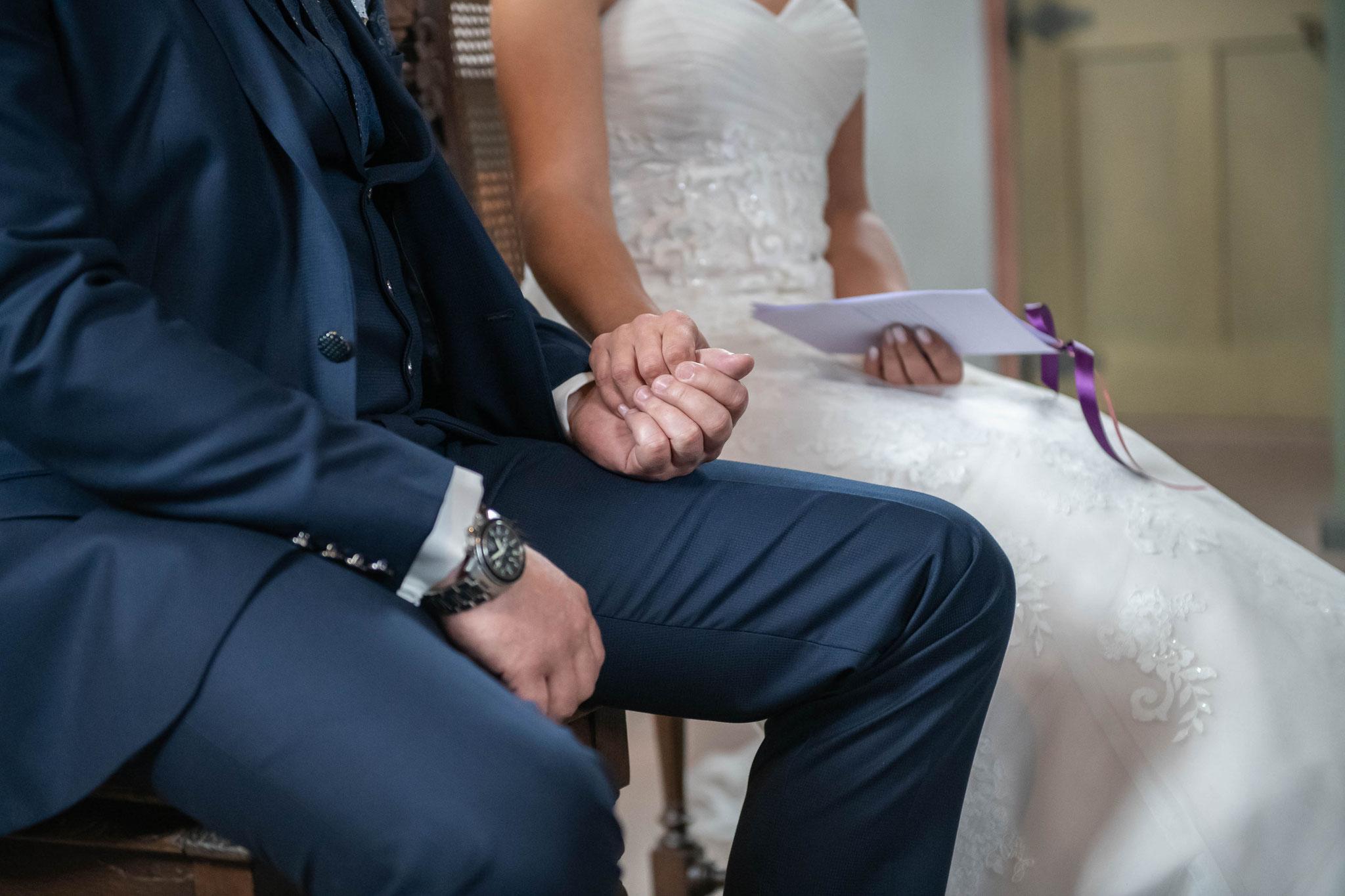 Braut und Bräutigam halten sich fest die Hände zusammen