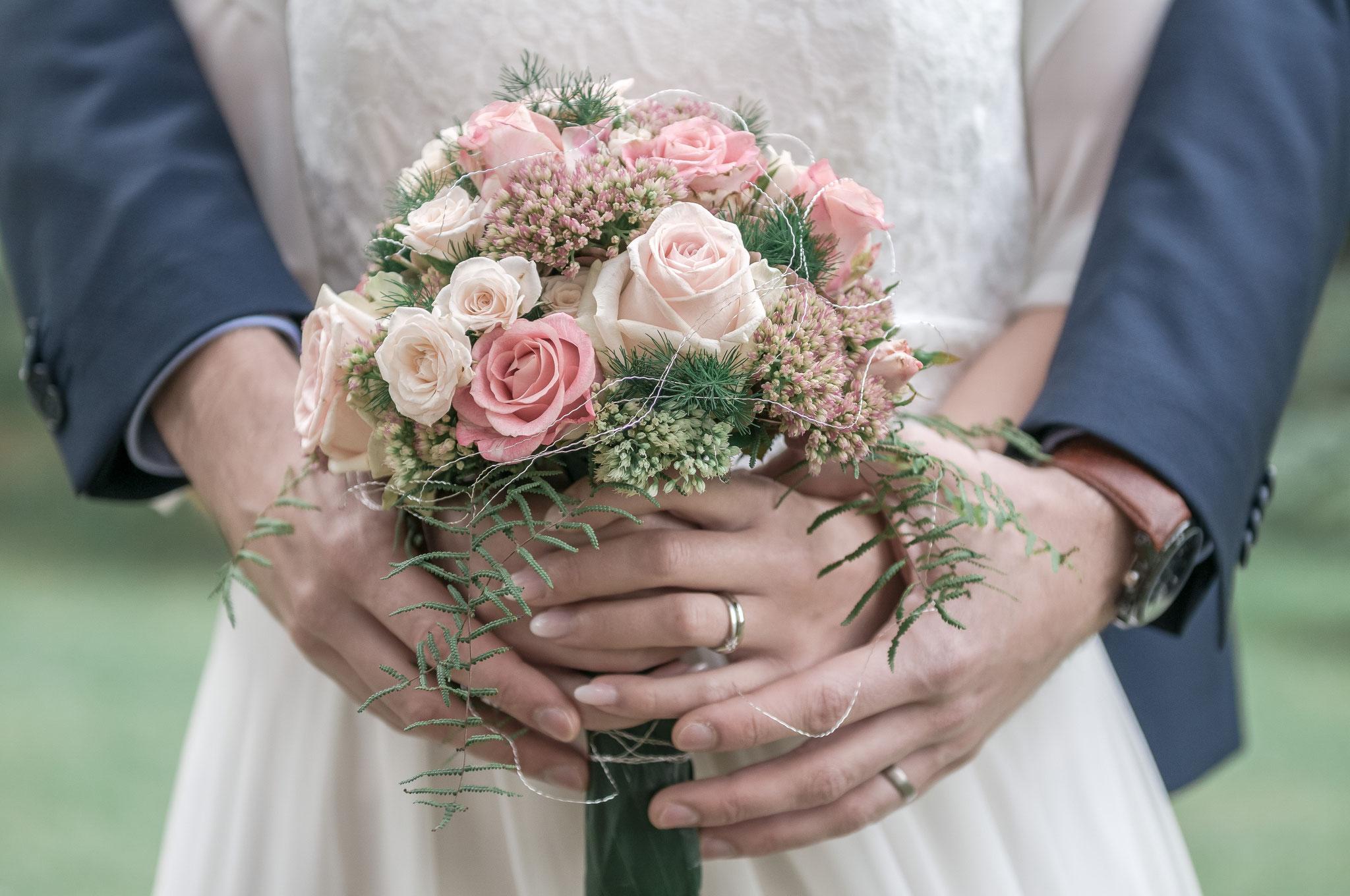 Braut und der Bräutigam halten den Hochzeitsdtrauß