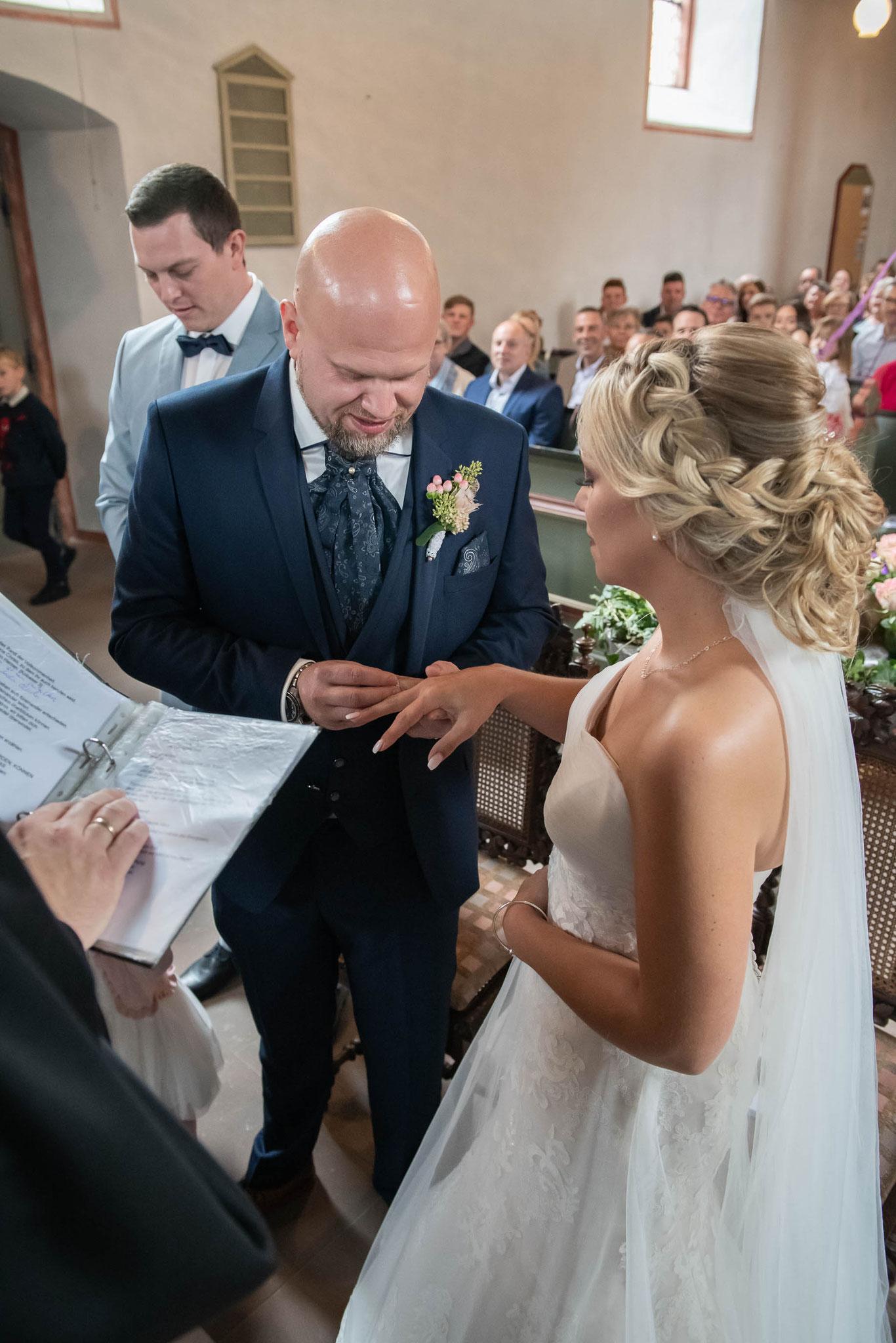 Bräutigam steckt der Braut den Trauring an