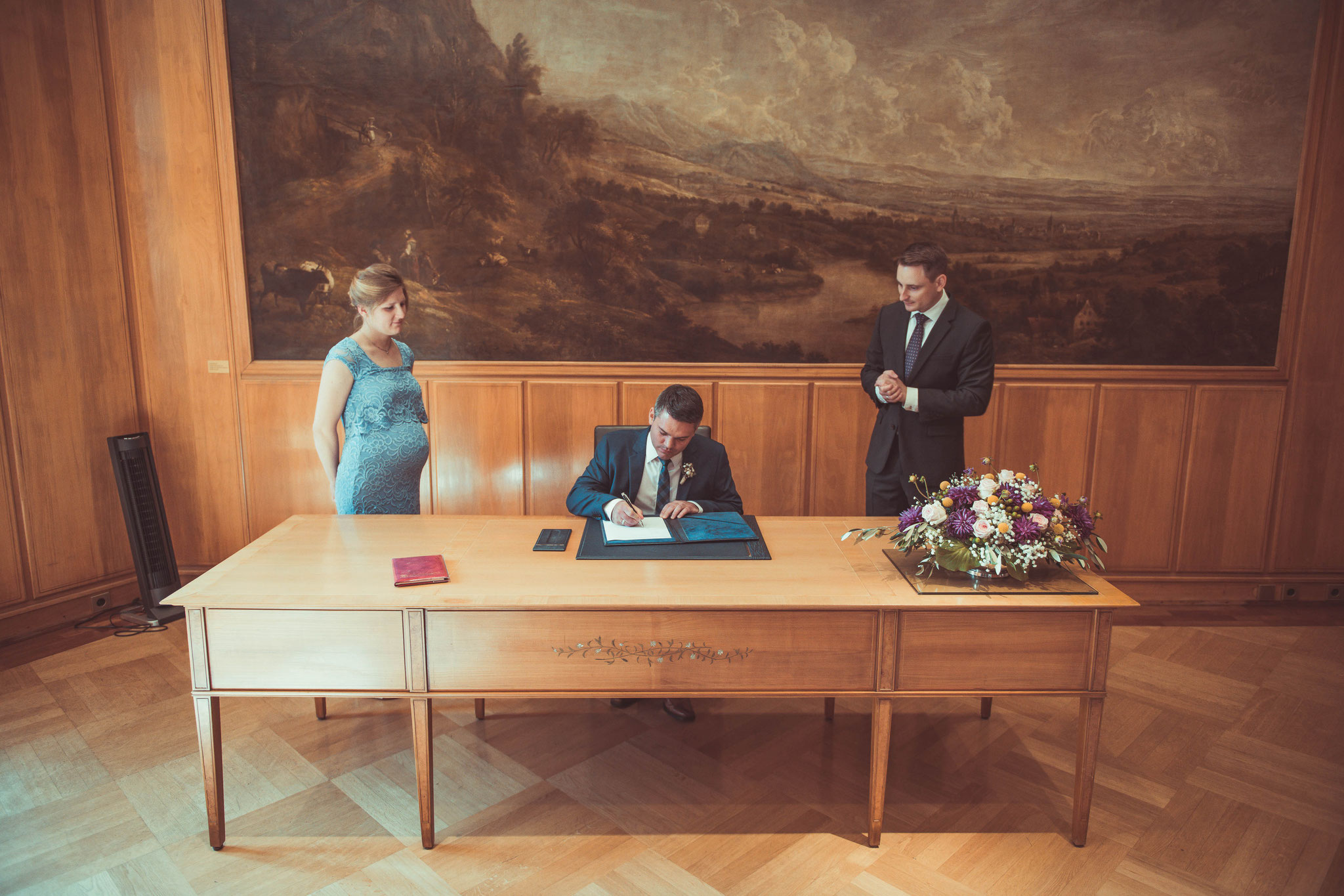 Bräutigam setzt seine Unterschrift auf das wichtigste Dokument