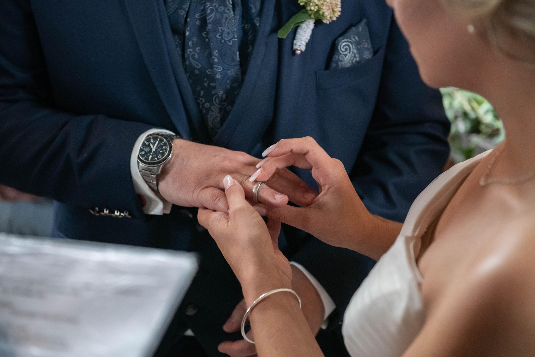 Braut steckt dem Bräutigam den Trauring an