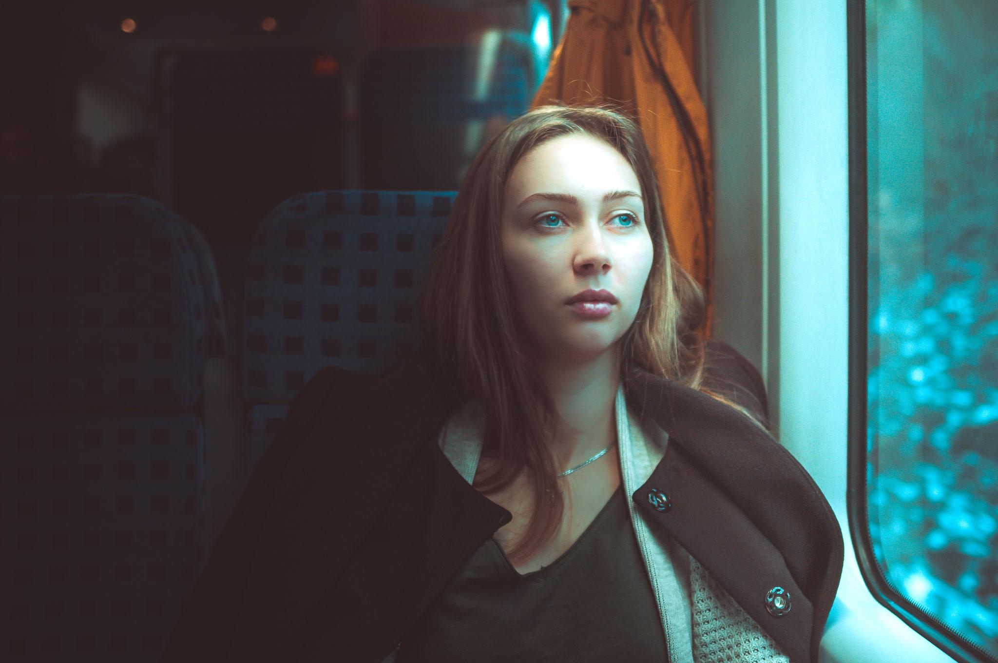 Junge hübsche Frau ganz in sich und nachdenklich unterwegs mit dem Zug