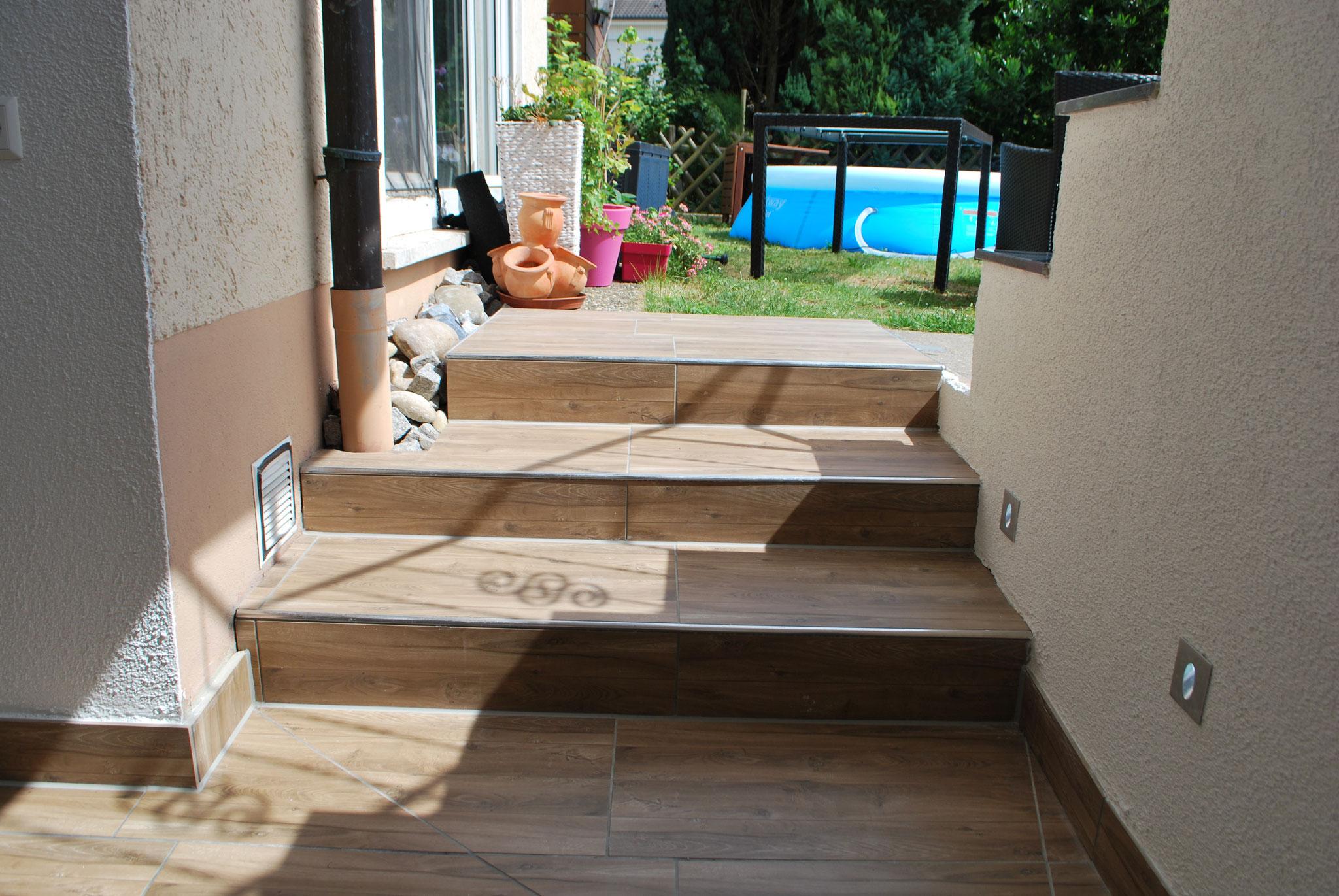 Treppe mit Holzoptikfliesen und Edeöstahlschienen