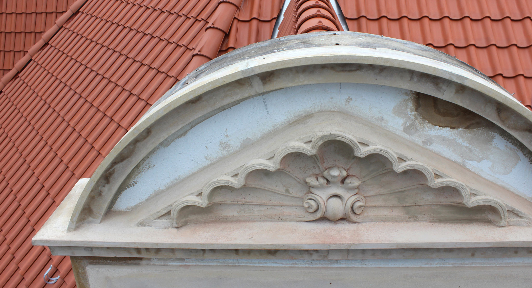 Rekonstruktion des Zwerchgiebels mit Stuckprofilen und Muschelwerk in Romanzementmörtel