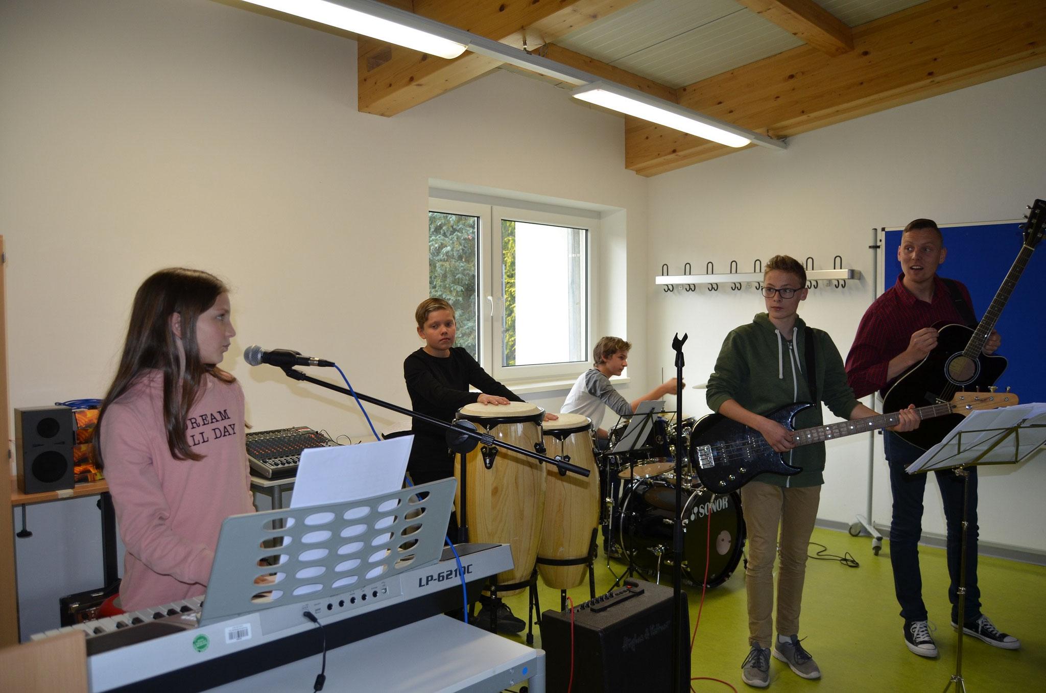 Alina, Felix, Raul und Joel werden vom Musiklehrer begleitet und gecoacht.