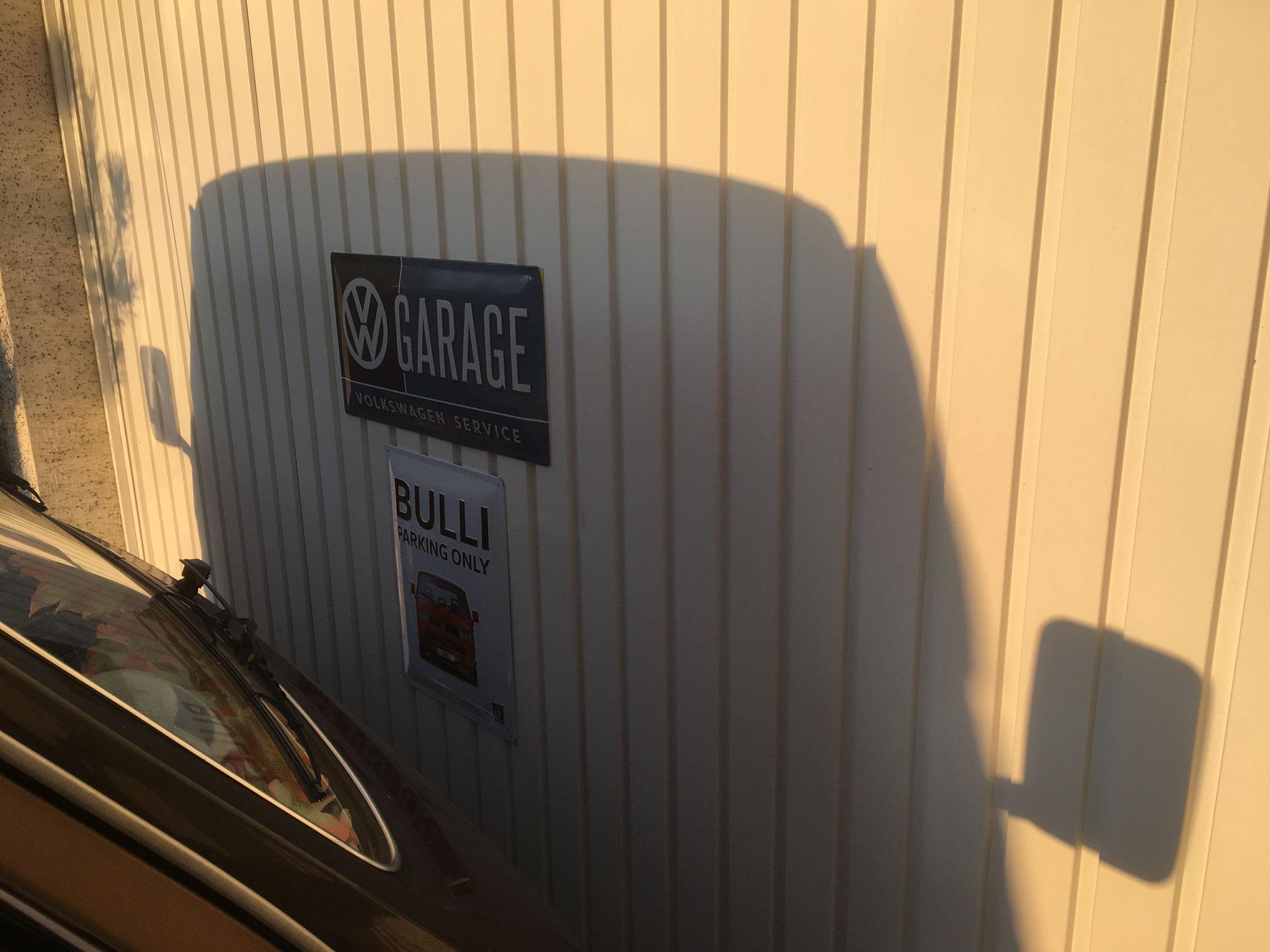 Wunderschöner Sonnenaufgang am Bulli. Schöne Silhouette an der Garagenwand.