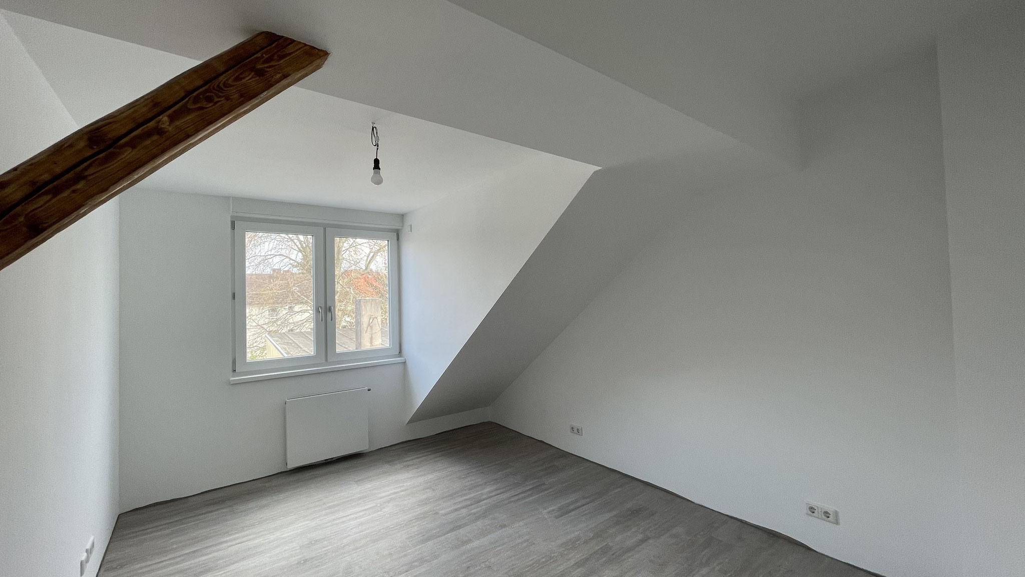 Die Innenansicht von einer Gaube mit verputzen Wänden