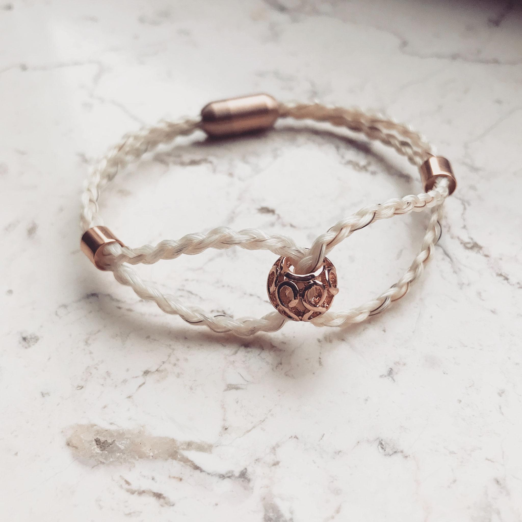 Schleifenarmband, 4-fach rund geflochten mit rosé Perlen und Edelstahl Magnetverschluss.