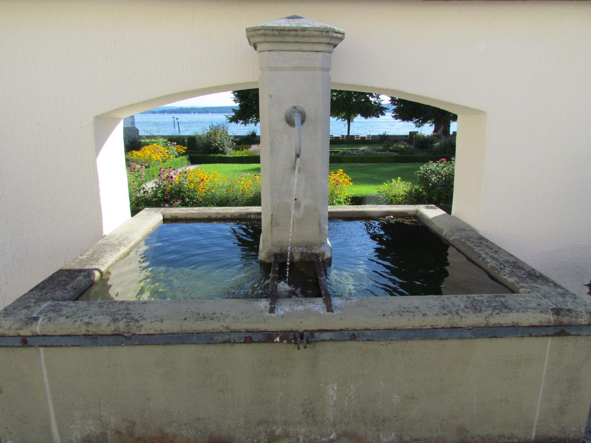 Klassischer Brunnen in einer Maueröffnung mit Blick zum See